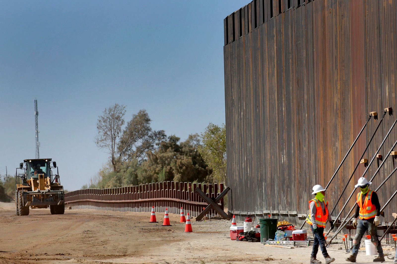 FILE - In this Sept. 10, 2019, file photo, government contractors erect a section of Pentagon-funded border wall along the Colorado River, in Yuma, Ariz. A federal appeals court hears arguments against diverting Pentagon money for border wall construction as time runs out. It says the Trump administration has moved quickly to spend the money after the Supreme Court rejected an emergency appeal to prevent work from starting in July. (AP Photo/Matt York,File)