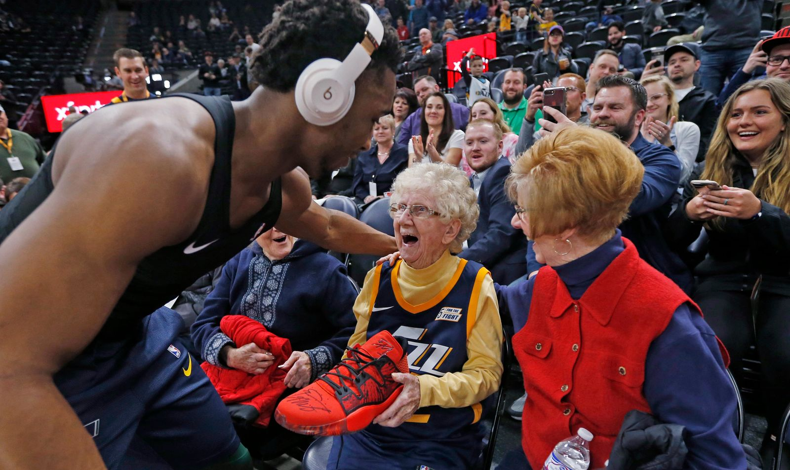 Utah Jazz guard Donovan Mitchell, left, hands his basketball shoe to Roberta Morgan, 102, after he warmed up for the team's NBA basketball game against the Milwaukee Bucks on Saturday, March 2, 2019, in Salt Lake City. (AP Photo/Rick Bowmer)