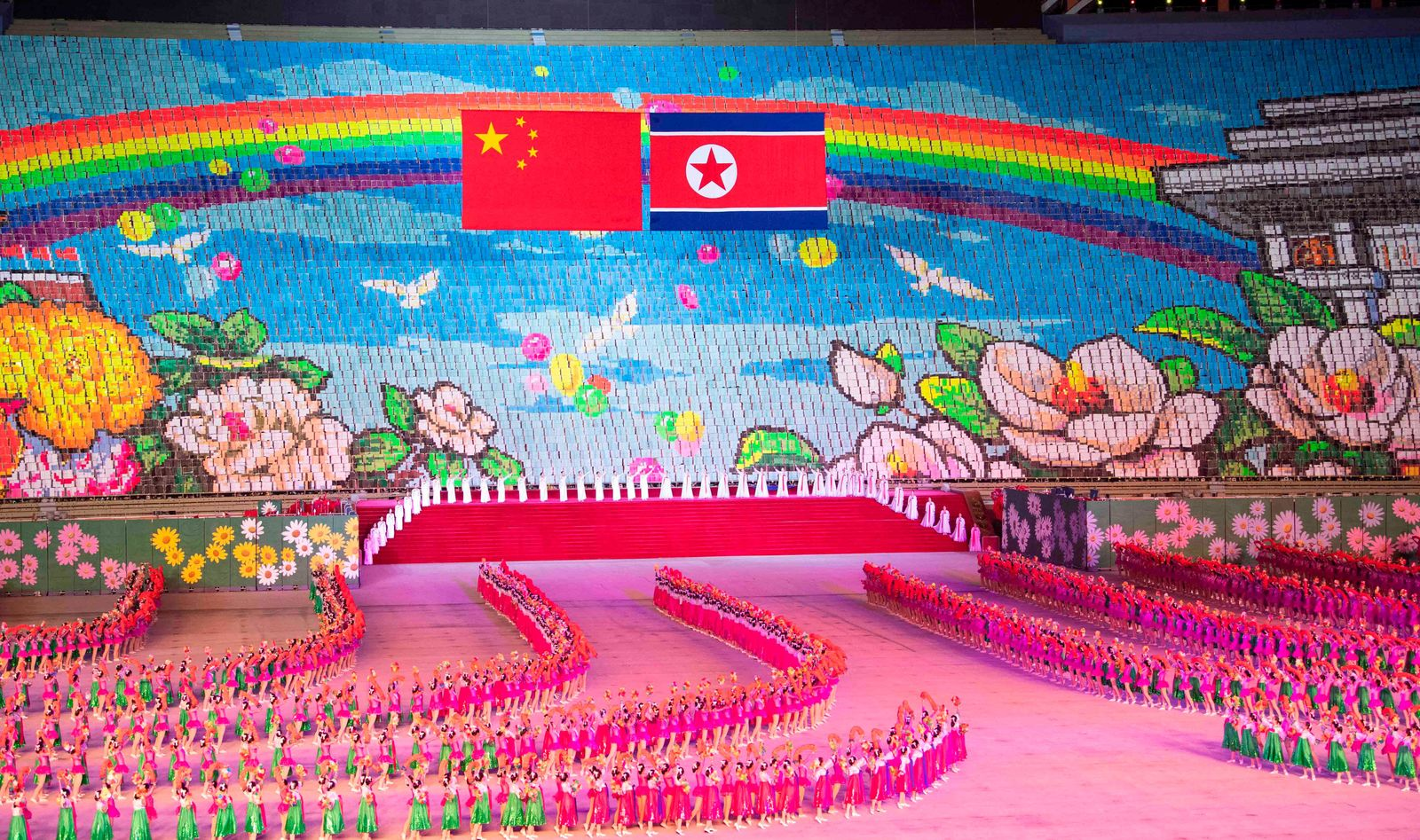 In this Thursday, June 20, 2019, photo released by China's Xinhua News Agency, Chinese, left, and North Korean flags are displayed during a mass gymnastic performance at the May Day Stadium in Pyongyang, North Korea. North Korean leader Kim Jong Un, meeting in Pyongyang with Chinese President Xi Jinping, said Thursday that his country is waiting for a desired response in stalled nuclear talks with the United States. (Shen Hong/Xinhua via AP)