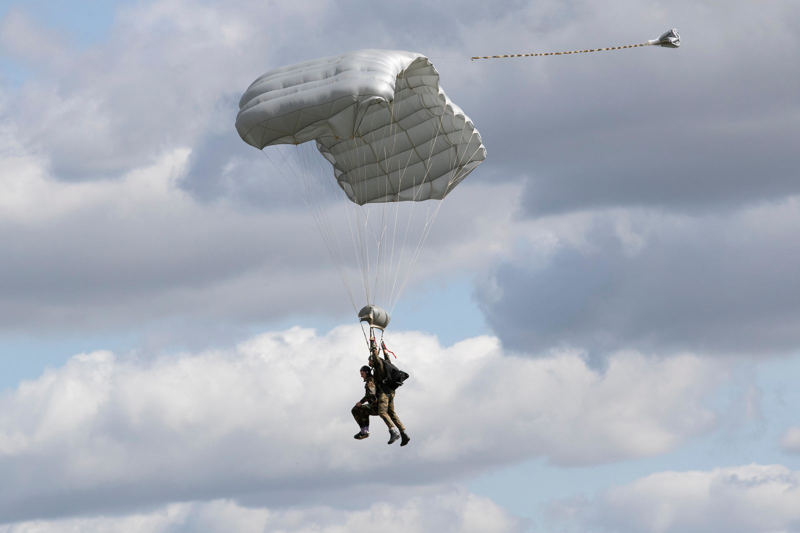Tom Rice, a 98-year-old American WWII veteran, front left, approaches the landing zone in a tandem parachute jump near Groesbeek, Netherlands, Thursday, Sept. 19, 2019, as part of commemorations marking the 75th anniversary of Operation Market Garden. Rice jumped with the U.S. Army's 101st Airborne Division in Normandy, landing safely despite catching himself on the exit and a bullet striking his parachute. (AP Photo/Peter Dejong)
