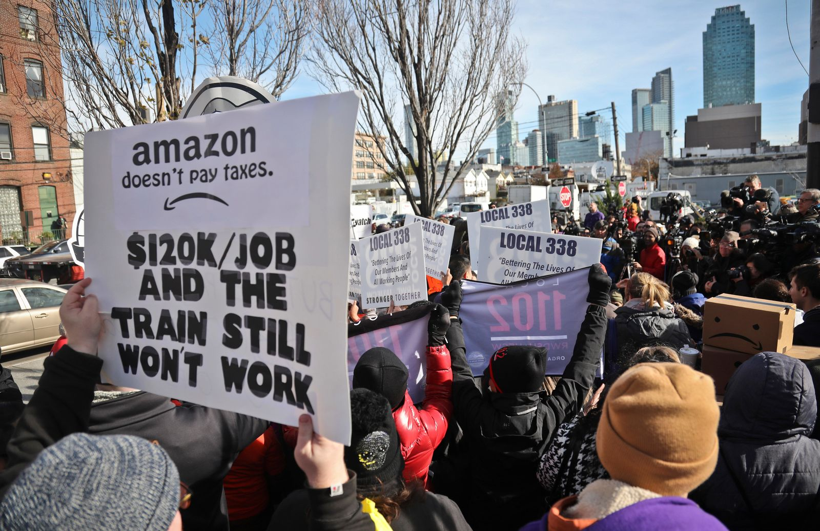 FILE - In this Nov. 14, 2018, file photo protesters carry anti-Amazon posters during a coalition rally and press conference opposing Amazon headquarters getting subsidies to locate in the New York neighborhood of Long Island City in the Queens borough of New York. Some residents wondered why one of the world's most valuable companies needed nearly $3 million in tax incentives to come to New York. (AP Photo/Bebeto Matthews, File)