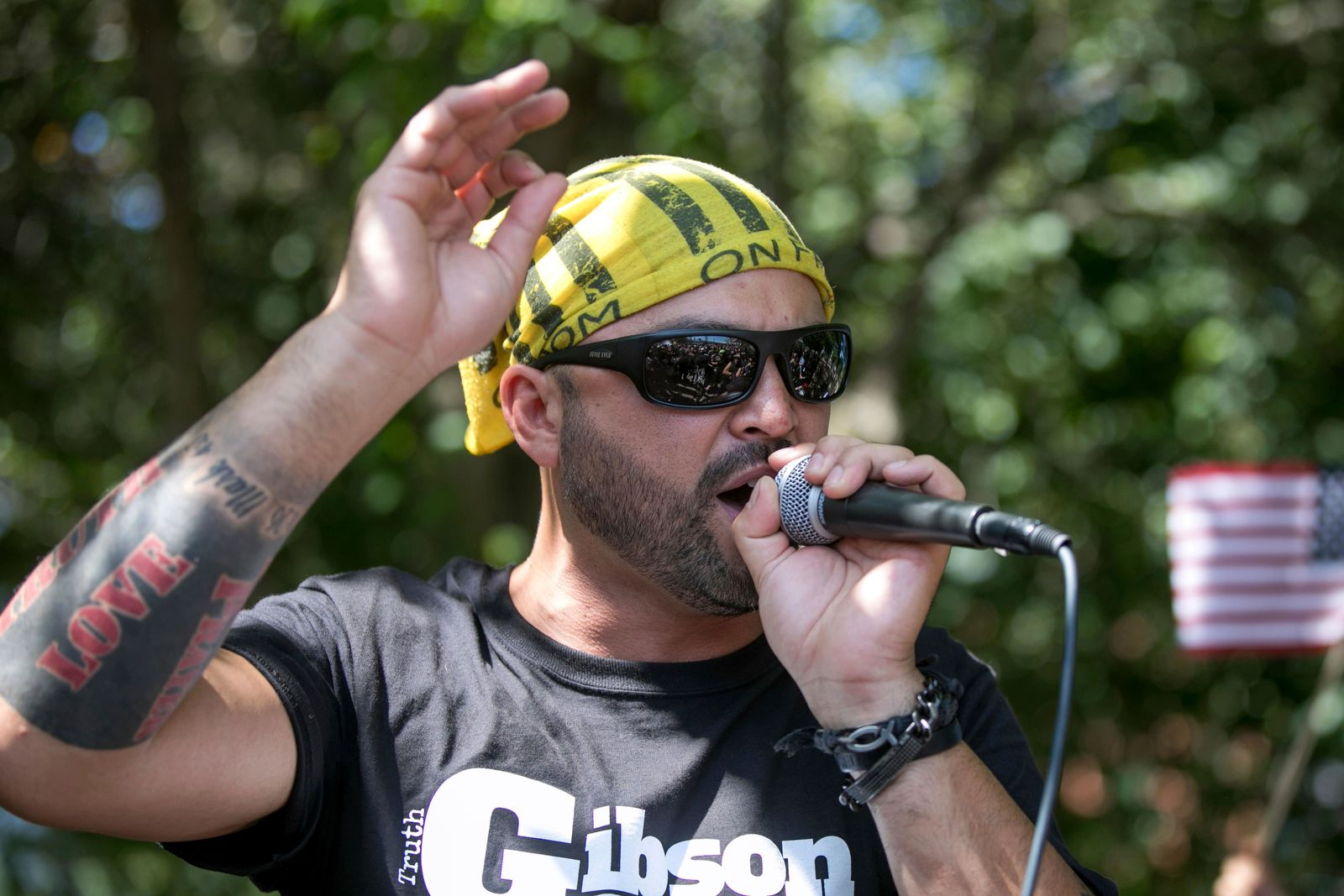 "FILE - In this Aug. 4, 2018 file photo, Patriot Prayer founder and rally organizer Joey Gibson speaks to his followers at a rally in Portland, Ore. On Friday, Aug. 16, 2019 authorities announced they've arrested Gibson, the leader of the right-wing group, on the eve of a far-right rally that's expected to draw people from around the U.S. to Portland on Saturday, Aug. 17, prompting Gibson to urge his followers to ""show up one hundred-fold"" in response. (AP Photo/John Rudoff, File)"