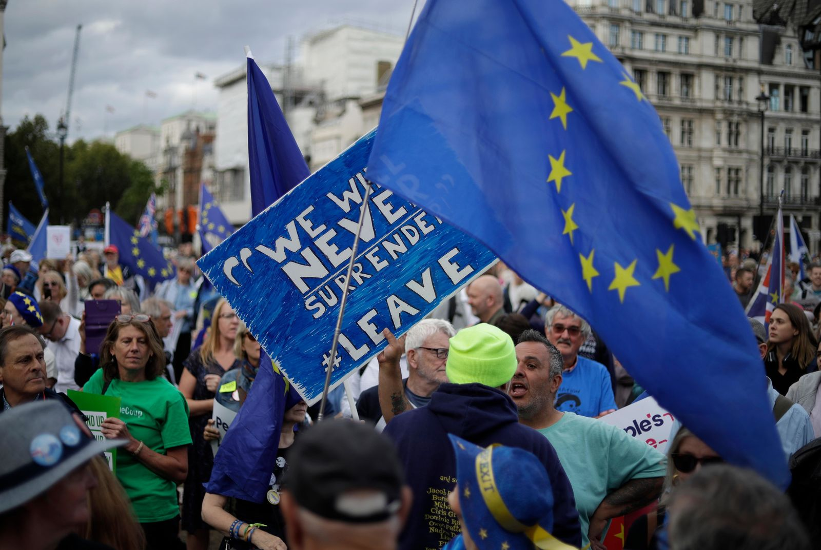 A leave supporter, left holding sign, tussles with a remain supporter, right holding EU flag, during a demonstration on Parliament Square in London, Wednesday, Sept. 4, 2019. (AP Photo/Matt Dunham)