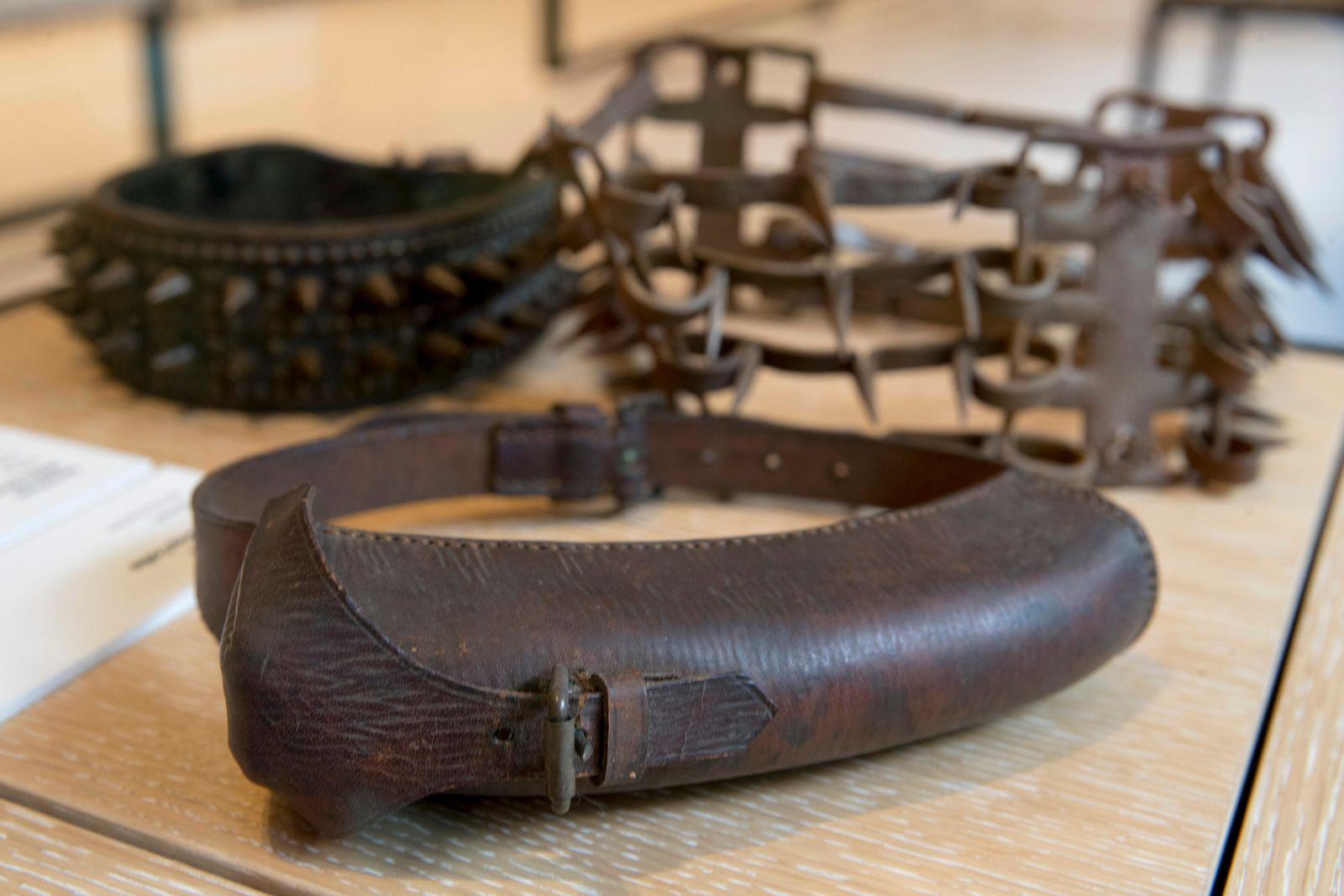 This Wednesday, Jan. 9, 2019, photo shows an American WWII messenger collar, foreground, on display next to other spike collars at the American Kennel Club Museum of the Dog in New York. The museum opens Feb. 8. (AP Photo/Mary Altaffer)