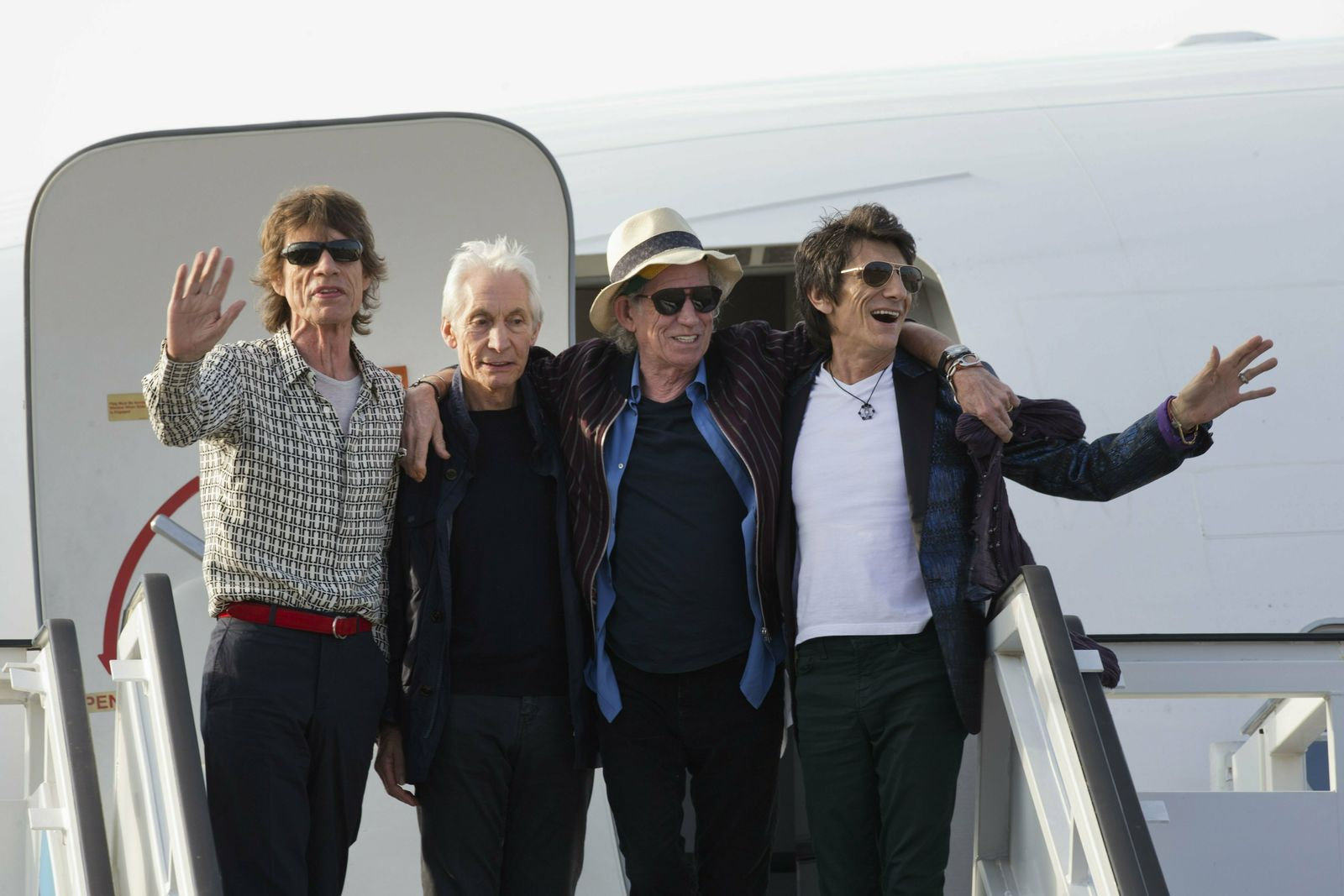 FILE - In this March 24, 2016 file photo, members of The Rolling Stones, from left, Mick Jagger, Charlie Watts, Keith Richards and Ron Wood pose for photos from the plane that brought them to Cuba at Jose Marti international airport in Havana, Cuba. The band plays Friday, June, 21, 2019 at Soldier Field in Chicago after a postponing their North American tour because frontman Mick Jagger needed medical treatment. A second show is scheduled for Tuesday at Soldier Field. (AP Photo/Ramon Espinosa File)