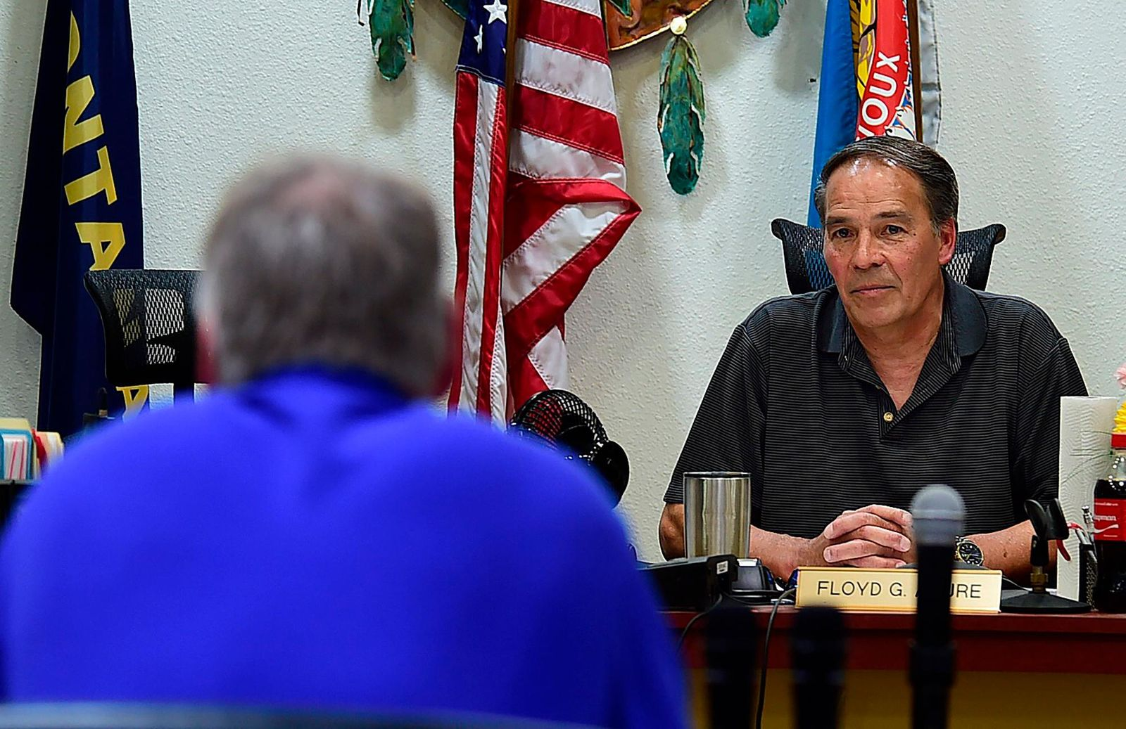 In this May 2018 file photo, Secretary of Interior Ryan Zinke, left, talks with Fort Peck Tribal Chairman Floyd Azure as Zinke met with residents in Fort Peck and the Fort Peck Tribal Council in Poplar, Mont. Major construction projects moving forward along the U.S. borders with Canada and Mexico amid the coronavirus pandemic are raising fears workers could spread infections within nearby communities, including several Native American tribes. Azure said an influx of pipeline workers to northeastern Montana could accelerate the spread of the virus that has so far spared the reservation. (Larry Mayer/The Billings Gazette via AP, File)