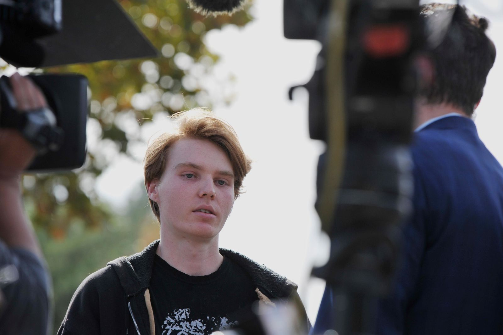 TV news reporters interview Ryan McCracken who lived next-door to the gunman who opened fire at Saugus High School on Thursday, Nov. 14, 2019 in Santa Clarita, Calif. (AP Photo by Christian Monterrosa)