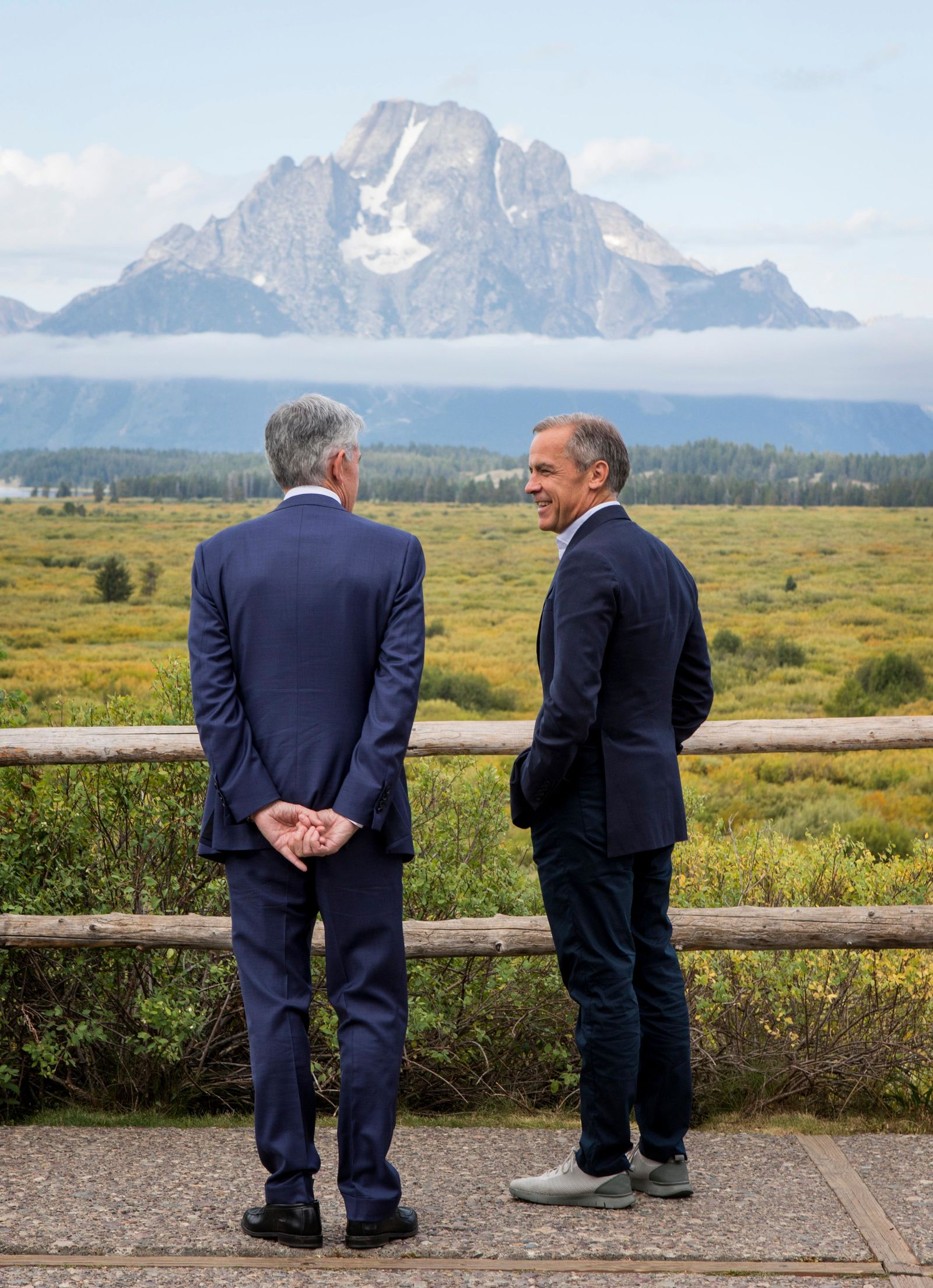 Federal Reserve Chairman Jerome Powell, left, and Bank of England Governor Mark Carney, right, pause in front of Mt. Moran after Powell's speech at the Jackson Hole Economic Policy Symposium on Friday, Aug. 23, 2019, in Jackson Hole, Wyo. (AP Photo/Amber Baesler)