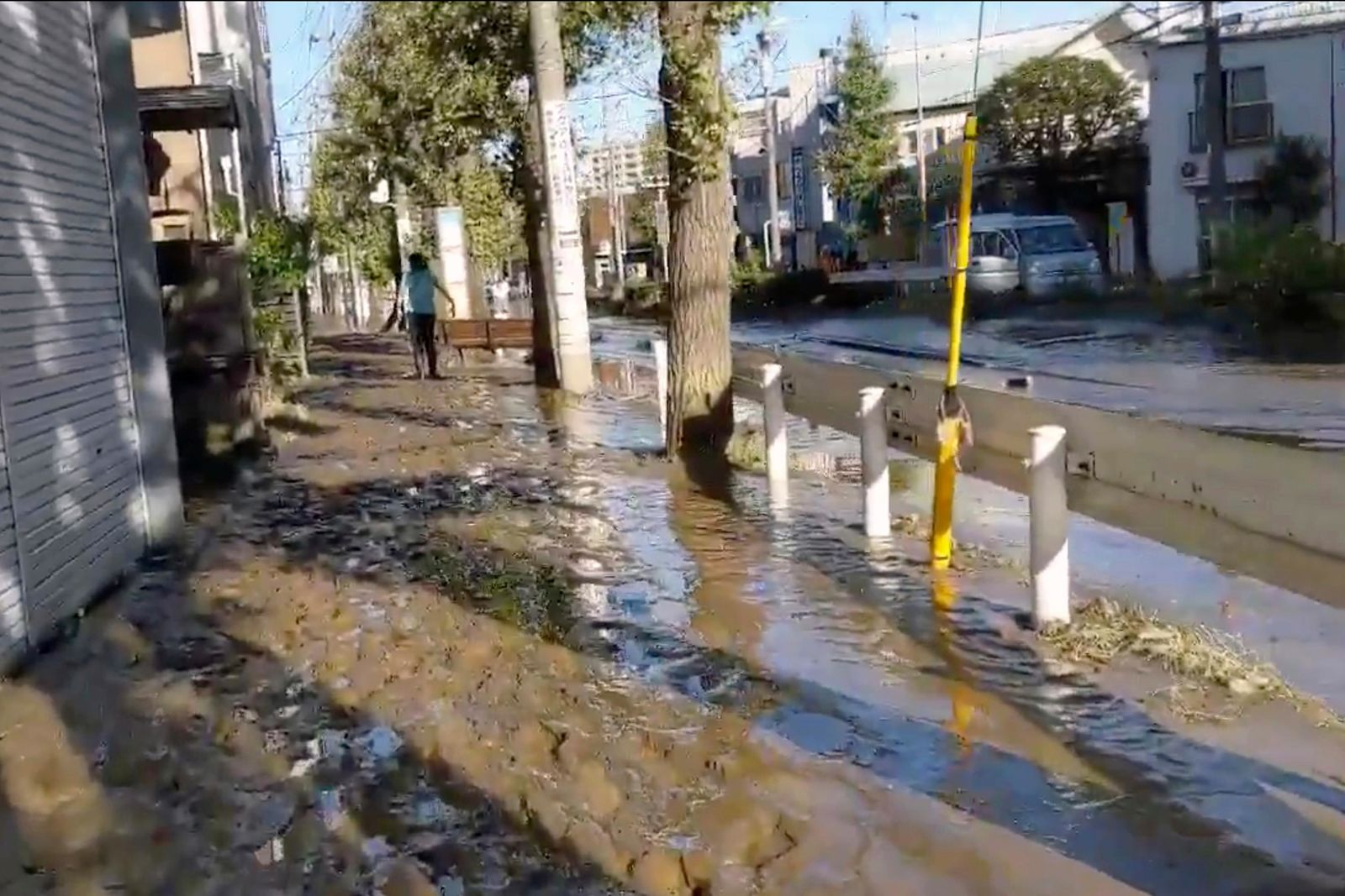 This image made from a video by @ar_kaz shows the mud covered street after the flood water receded on the morning Sunday, Oct. 13, 2019, in Kawasaki, near Tokyo, Japan. (@ar_kaz via AP)