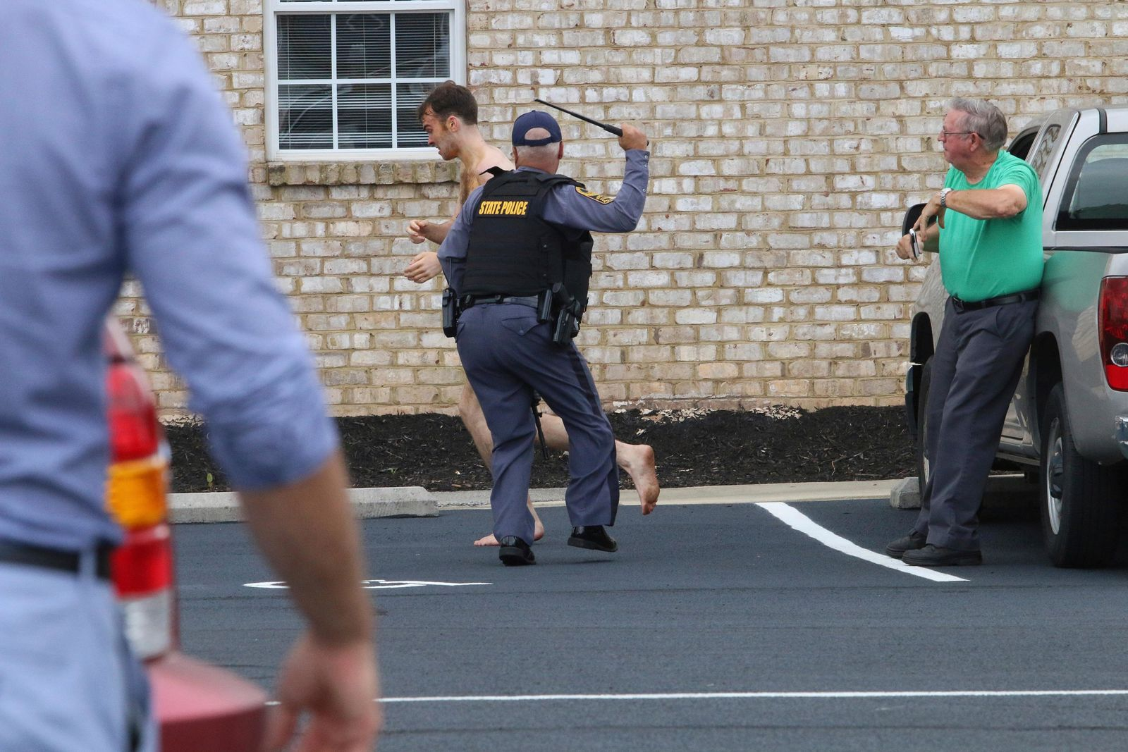 State Police chase Matthew Thomas Bernard after attacking Keeling Baptist Church groundskeeper Loyd Gauldin, right, on Tuesday, Aug. 27, 2019 in Keeling, Va. (Matt Bell/Star-Tribune Chatham, Va. via AP)