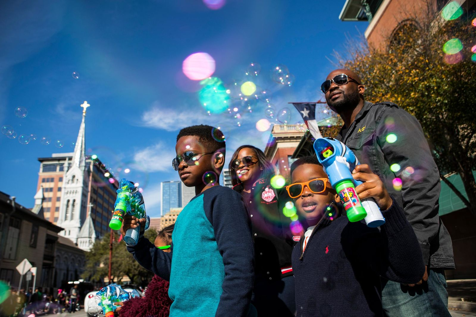 "In this Monday, Jan. 15, 2018 photo,  Jaylen Chukudebelu, left, and his brother, Cameron, blow bubbles as they watch The ""Original"" MLK, Jr. Parade with their parents, Khia and Chuk, in front of Minue Maid Park in Houston. (Brett Coomer/Houston Chronicle via AP)"
