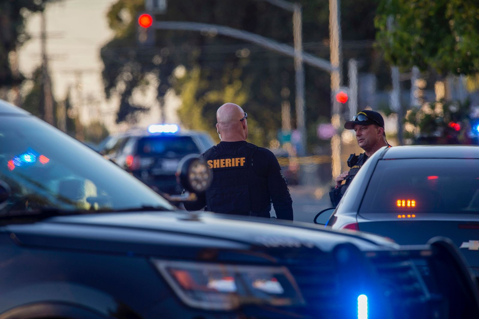 Sacramento County Sheriff's Department deputies talk, Wednesday, June 19, 2019, on Grove Avenue in Sacramento, Calif., where an armed subject fired on police officers. (Daniel Kim/The Sacramento Bee via AP)
