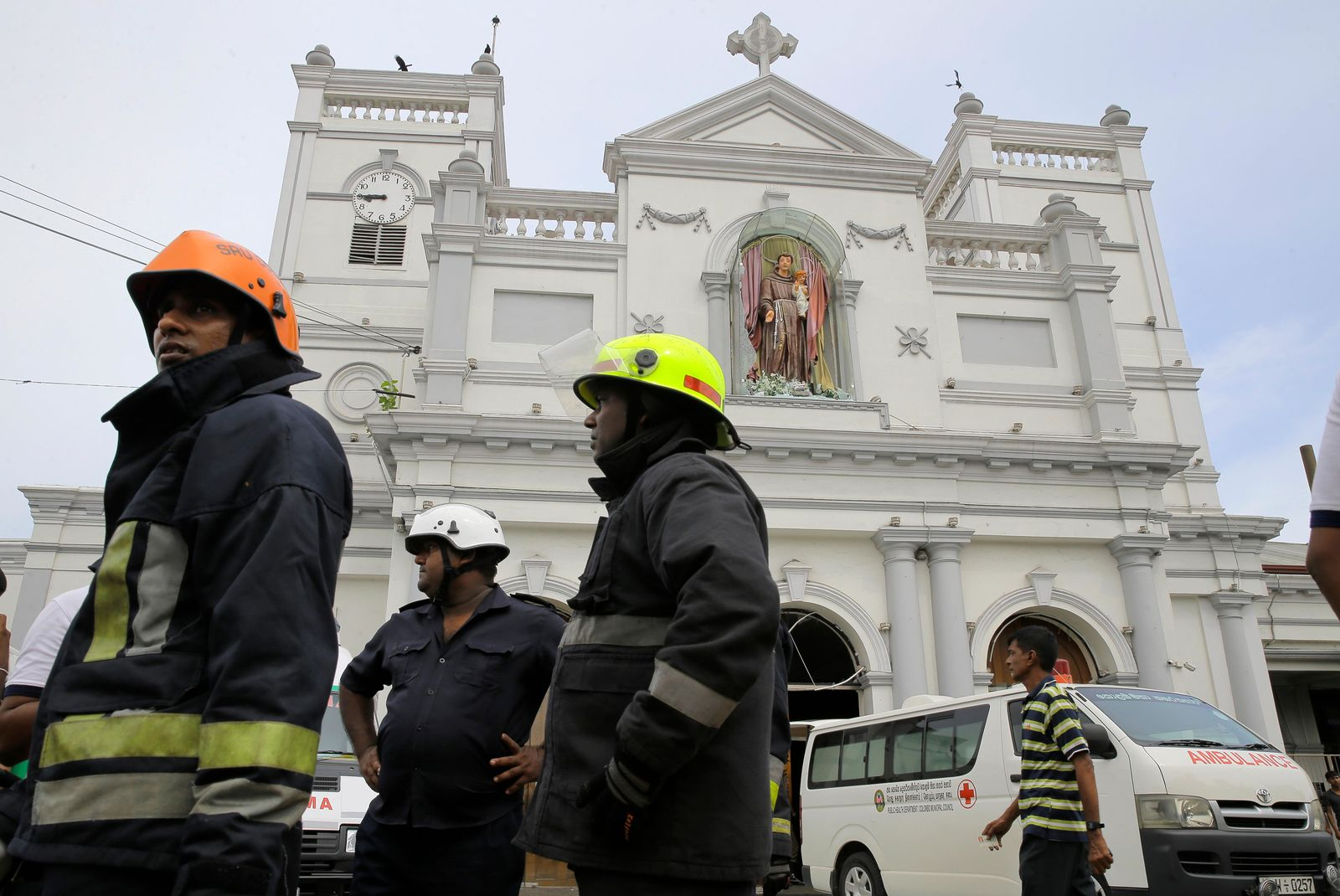 Sri Lankan firefighters stand in the area around St. Anthony's Shrine after a blast in Colombo, Sri Lanka, Sunday, April 21, 2019. Witnesses are reporting two explosions have hit two churches in Sri Lanka on Easter Sunday, causing casualties among worshippers. (AP Photo/Eranga Jayawardena)