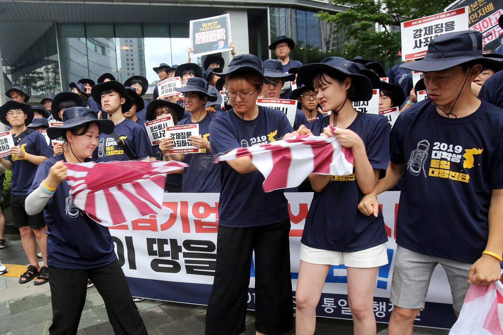 South Korean college students tear a banner showing an image of a Japanese rising sun flag during a rally to denounce Japan's new trade restrictions on South Korea in front of the office of Mitsubishi Corp. in Seoul, South Korea, Wednesday, Aug. 7, 2019.{ } (AP Photo/Ahn Young-joon)