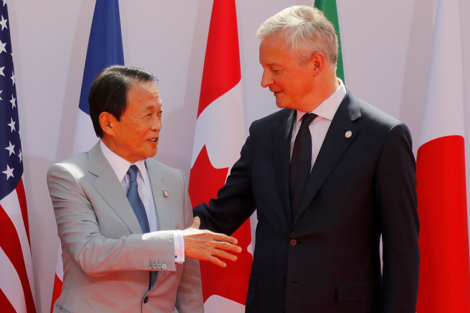 French Finance Minister Bruno Le Maire, right, welcomes Japan's Finance Minister Taro Aso at the G-7 Finance Wednesday July 17, 2019. (AP Photo/Michel Euler)