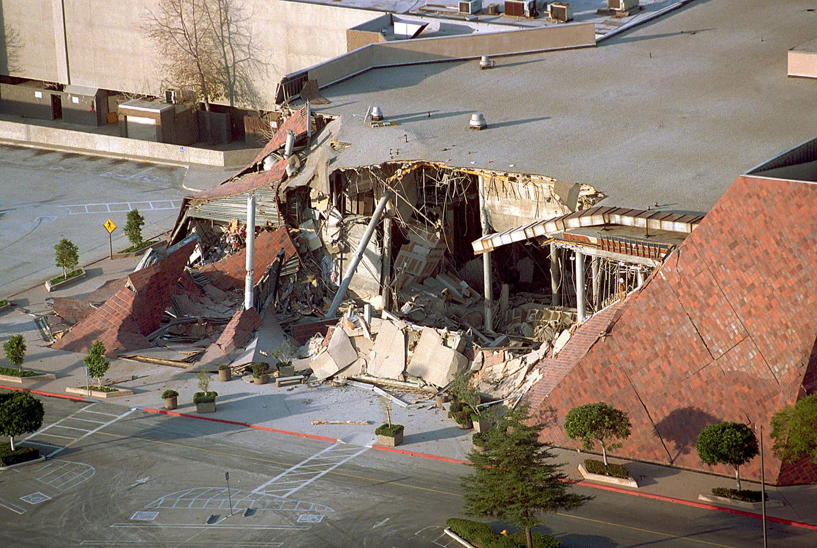 FILE - This Jan. 17, 1994 file photo shows a portion of the Bullock's department store in Los Angeles' Northridge Fashion Center that collapsed in the Northridge earthquake. Twenty-five years ago this week, a violent, pre-dawn earthquake shook Los Angeles from its sleep, and sunrise revealed widespread devastation, with dozens killed and $25 billion in damage. (AP Photo/Reed Saxon, File)