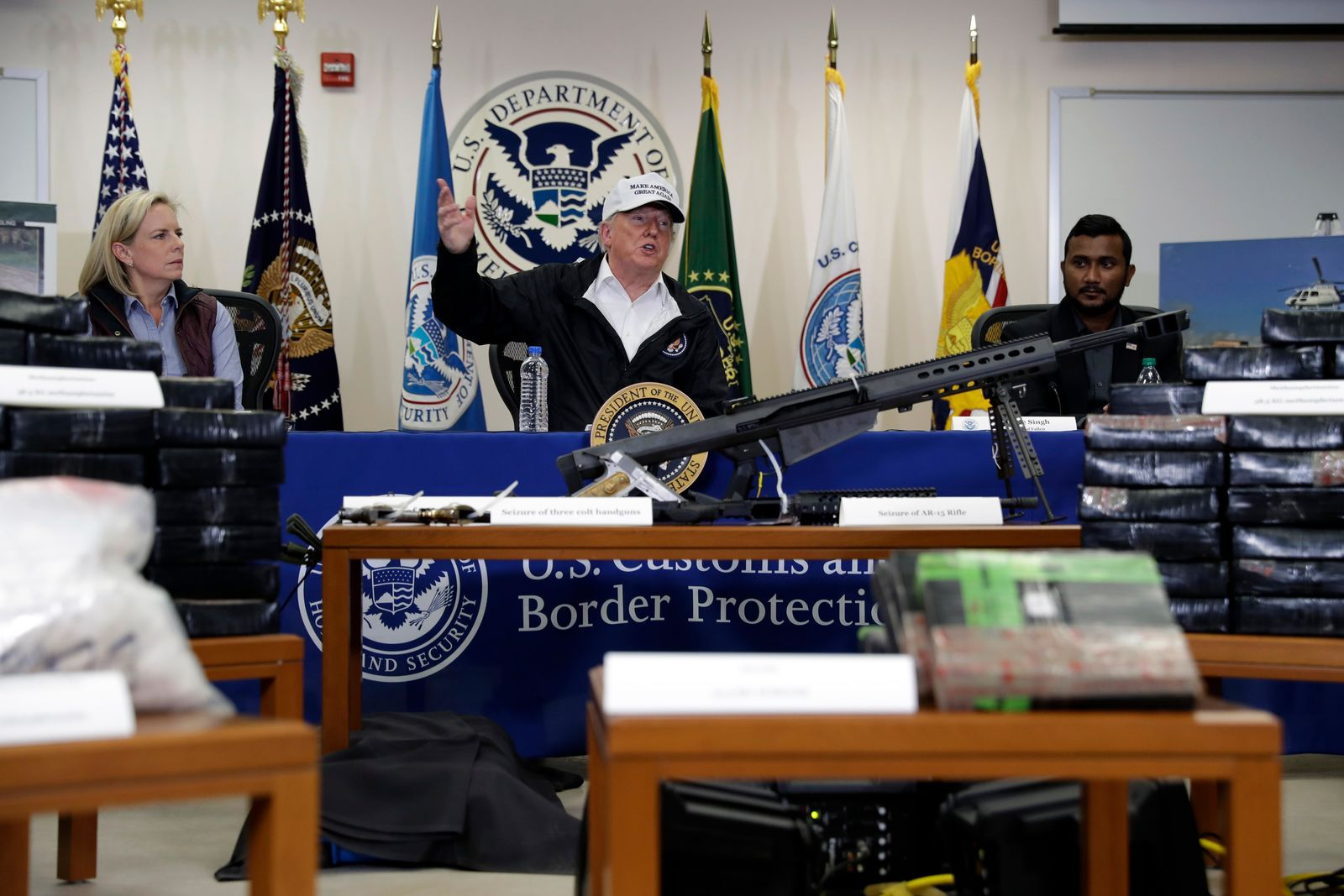 With weapons and illegal that have been seized by U.S. Customs and Border Protection in the foreground, President Donald Trump speaks at a roundtable on immigration and border security at U.S. Border Patrol McAllen Station, during a visit to the southern border, Thursday, Jan. 10, 2019, in McAllen, Texas. (AP Photo/ Evan Vucci)
