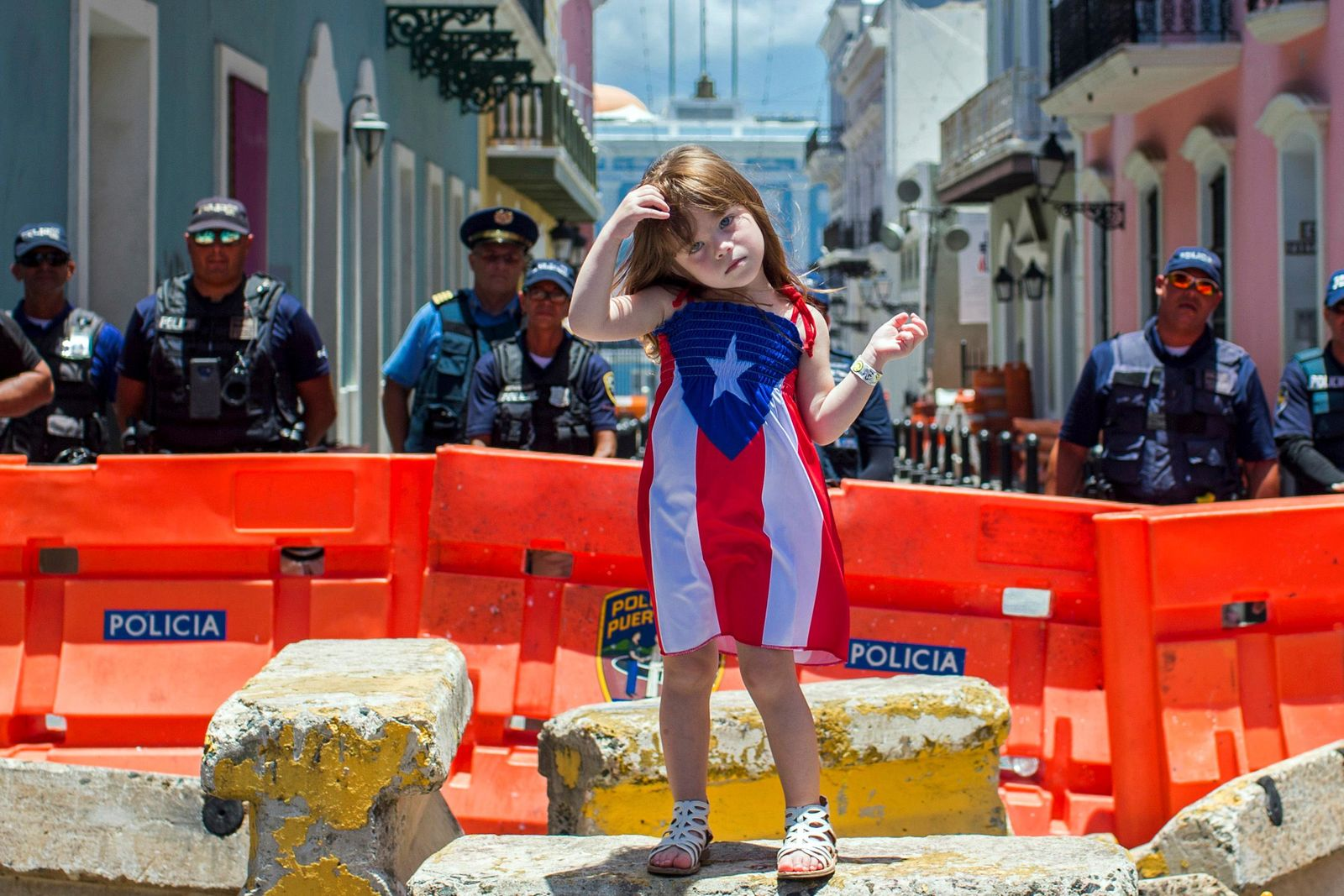 A girl wearing a dress featuring the Puerto Rican flag stands in front of police blocking the road leading to the La Fortaleza governor's mansion in San Juan, Puerto Rico, Thursday, July 18, 2019. (AP Photo/Dennis M. Rivera Pichardo)