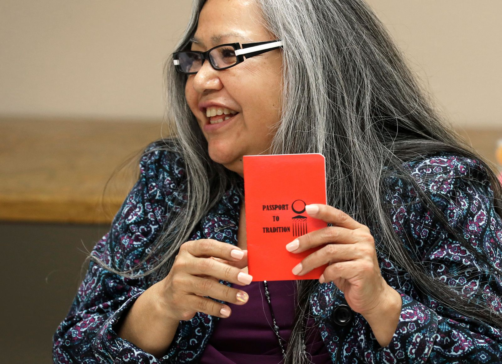 "Annette Squetimkin-Anquoe, a member of the Colville Indian tribe and the Chief Traditional Health Officer at the Urban Indian Health Institute in Seattle, holds a booklet with a cover that reads ""Passport to Tradition,"" Friday, Jan. 11, 2019, during a talking circle meeting to discuss the practice of traditional Indian medicine with employees of the Seattle Indian Health Board.   Fallout from the federal government shutdown is hurting hundreds of Native American tribes and entities that serve them. The pain is especially deep in tribal communities with high rates of poverty and unemployment, and where one person often supports an extended family.  (AP Photo/Ted S. Warren)"