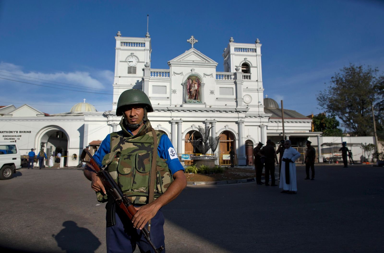 Sri Lankan air force officers and clergy stand outside St. Anthony's Shrine, a day after a blast in Colombo, Sri Lanka, Monday, April 22, 2019.{ } (AP Photo/Gemunu Amarasinghe)