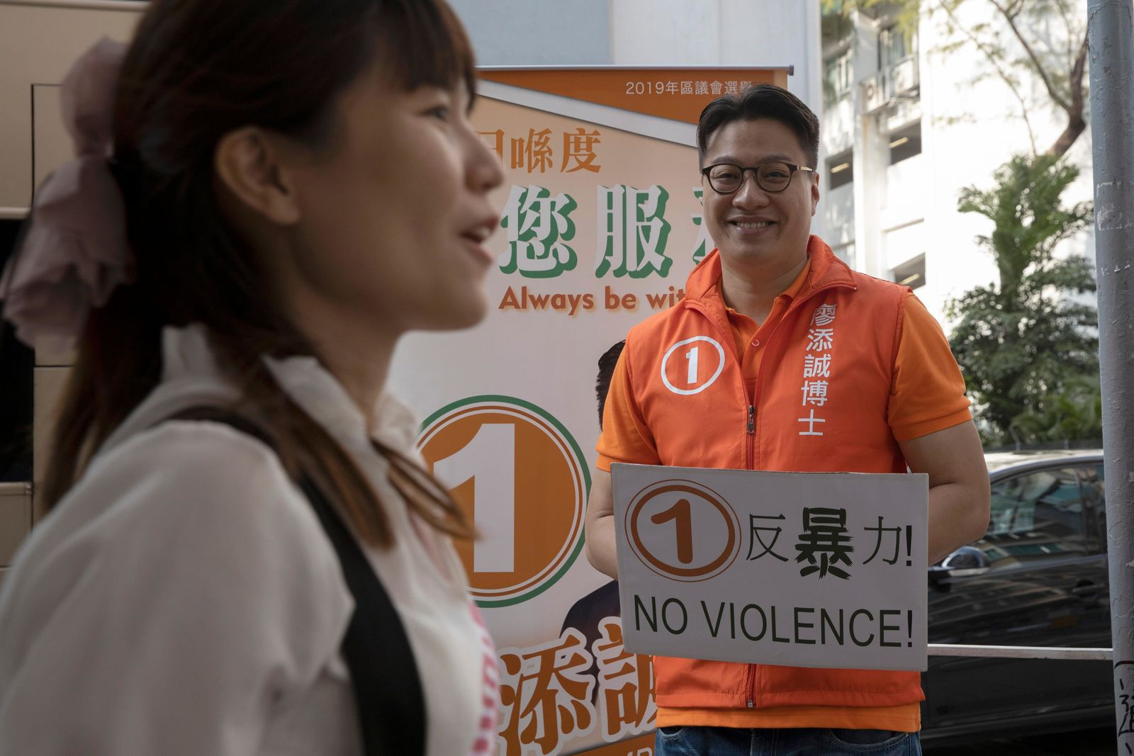 Independent candidate Dr. Liu Ting-Shing Marcus reacts as Clarisse Yeung of the KICKSTART Wan Chai party passes by during their campaigning in the Tai Hang constituency in Hong Kong on Saturday, Nov. 23, 2019. Sunday's low-level polls for district councillor have emerged as a pivotal bellwether on public support for increasingly violent protests, that had disrupted life in Asia's top financial hub for months. (AP Photo/Ng Han Guan)