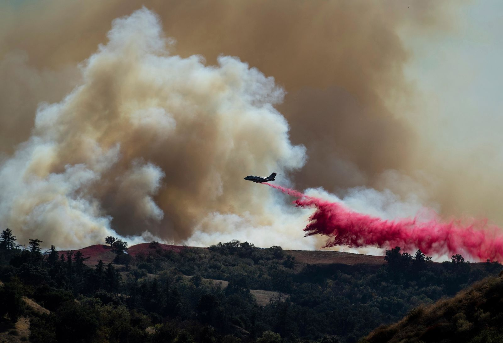 A tanker drops retardant on the Saddleridge Fire burning in Newhall, Calif., on Friday, Oct. 11, 2019. (AP Photo/Noah Berger)