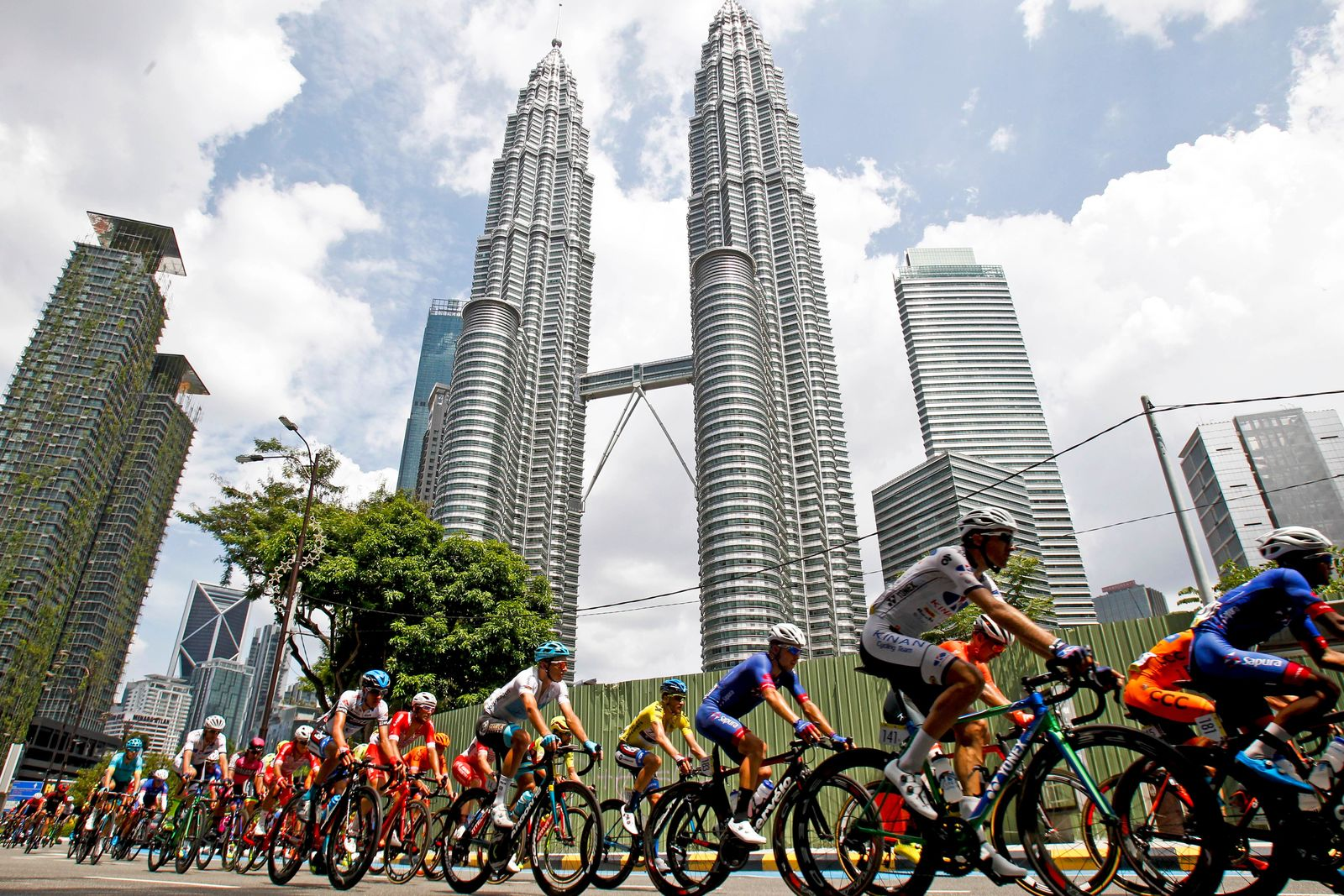 FILE - In this March 25, 2018 file photo, cyclists move past Malaysia's landmark Petronas Twin Towers during the last stage of Le Tour de Langkawi cycling race in Kuala Lumpur, Malaysia. (AP Photo/Sadiq Asyraf, File)
