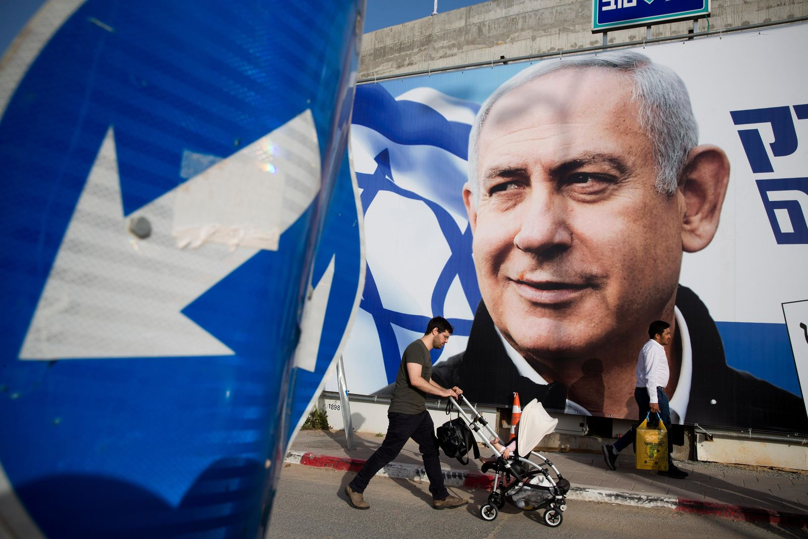 FILE - In this April 7, 2019 file photo, a man walks by an election campaign billboard showing Israel's Prime Minister Benjamin Netanyahu, the Likud party leader, in Tel Aviv, Israel. (AP Photo/Oded Balilty, File)