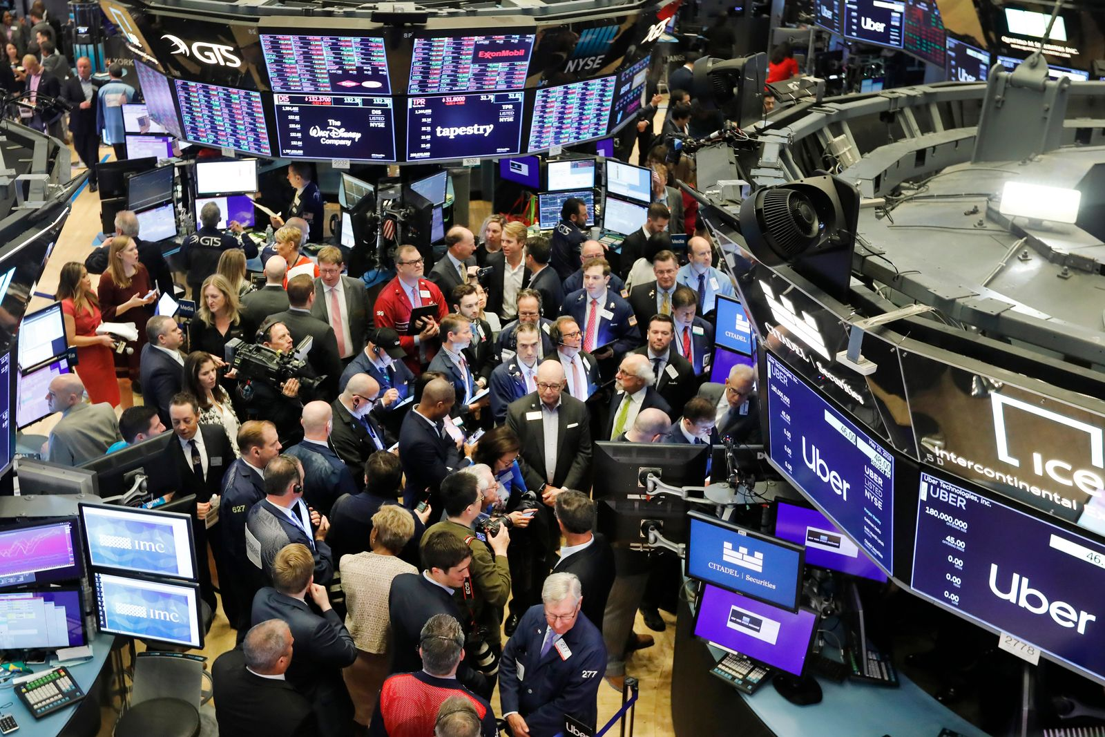 Stock traders gather around the post where Uber shares will begin trading during the company's initial public offering at the New York Stock Exchange, Friday, May 10, 2019. (AP Photo/Richard Drew)