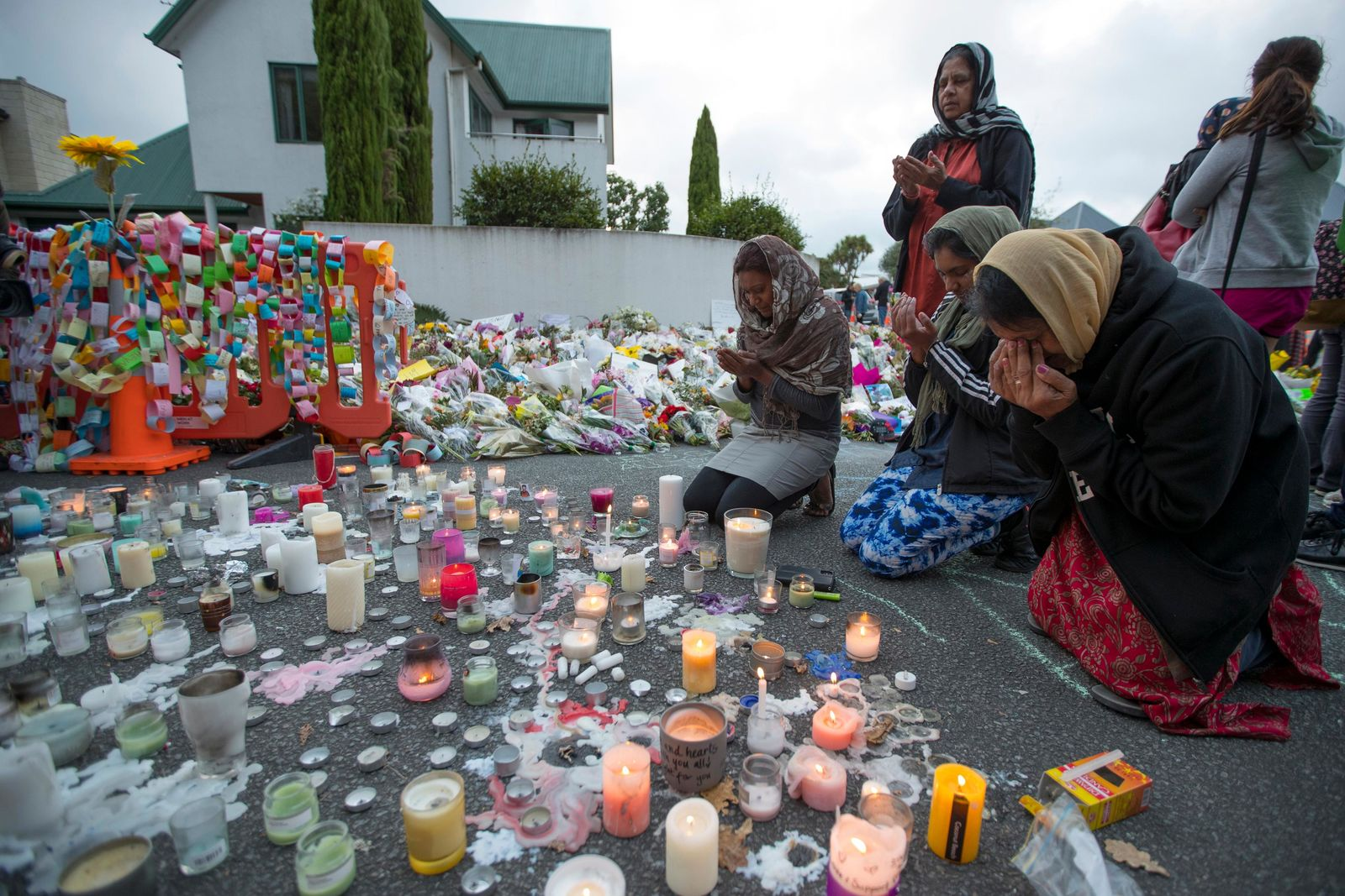 People mourn at a makeshift memorial site near the Al Noor mosque in Christchurch, New Zealand, Tuesday, March 19, 2019. (AP Photo/Vincent Thian)