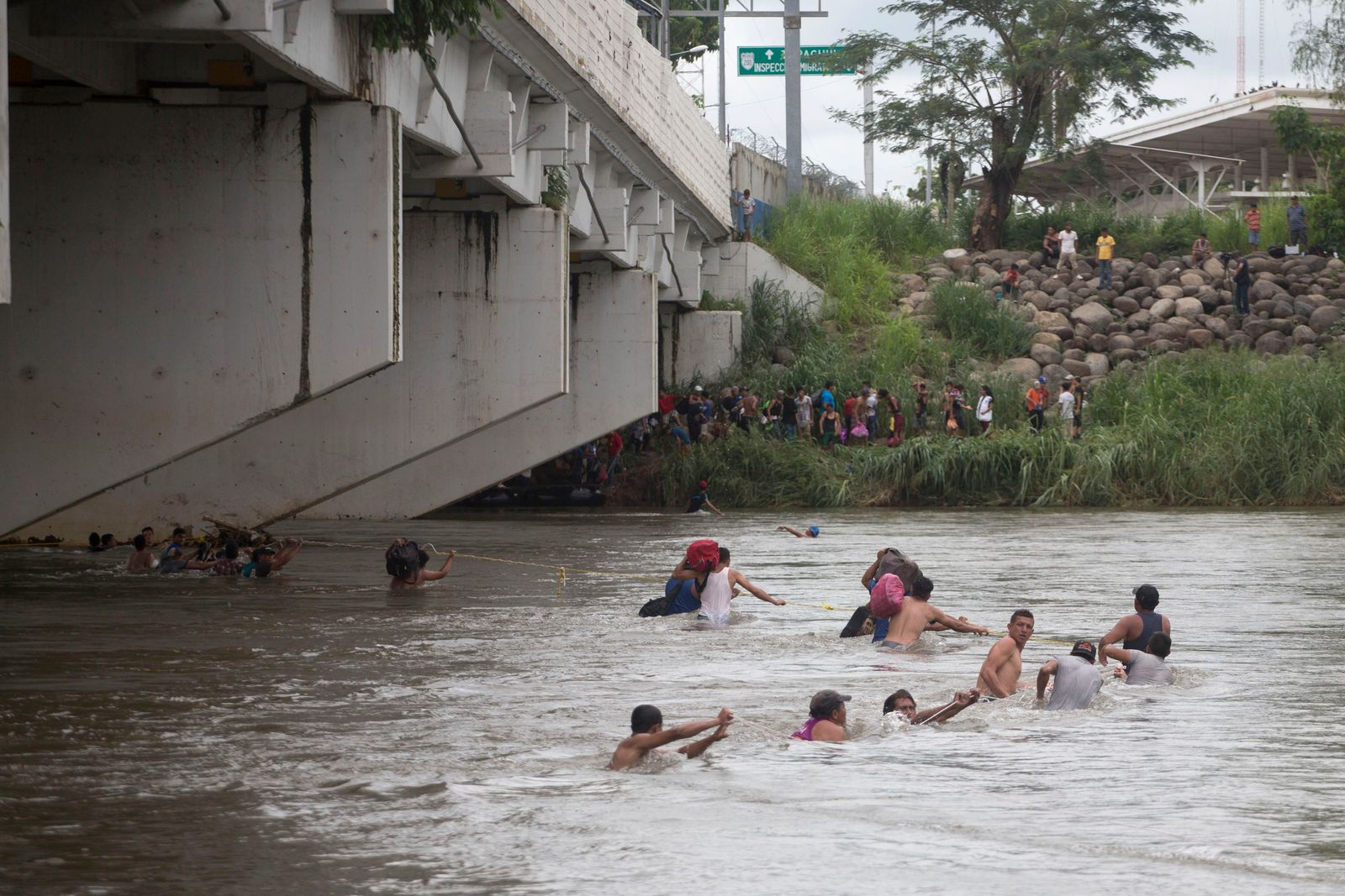 A group of Central American migrants wade across the Suchiate River, on the the border between Guatemala and Mexico, in Ciudad Hidalgo, Mexico, Saturday, Oct. 20, 2018. (AP Photo/Moises Castillo)