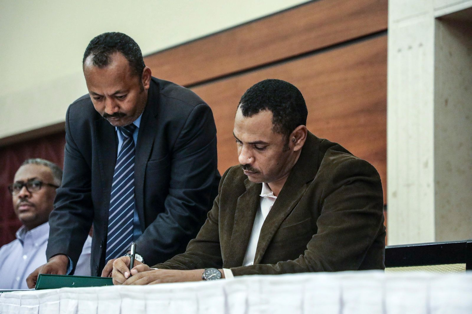 Sudan's pro-democracy movement leader Ahmad al-Rabiah signs a power sharing document with the ruling military council in Khartoum, Sudan, Wednesday, July 17, 2019.{ } (AP Photo/Mahmoud Hjaj)