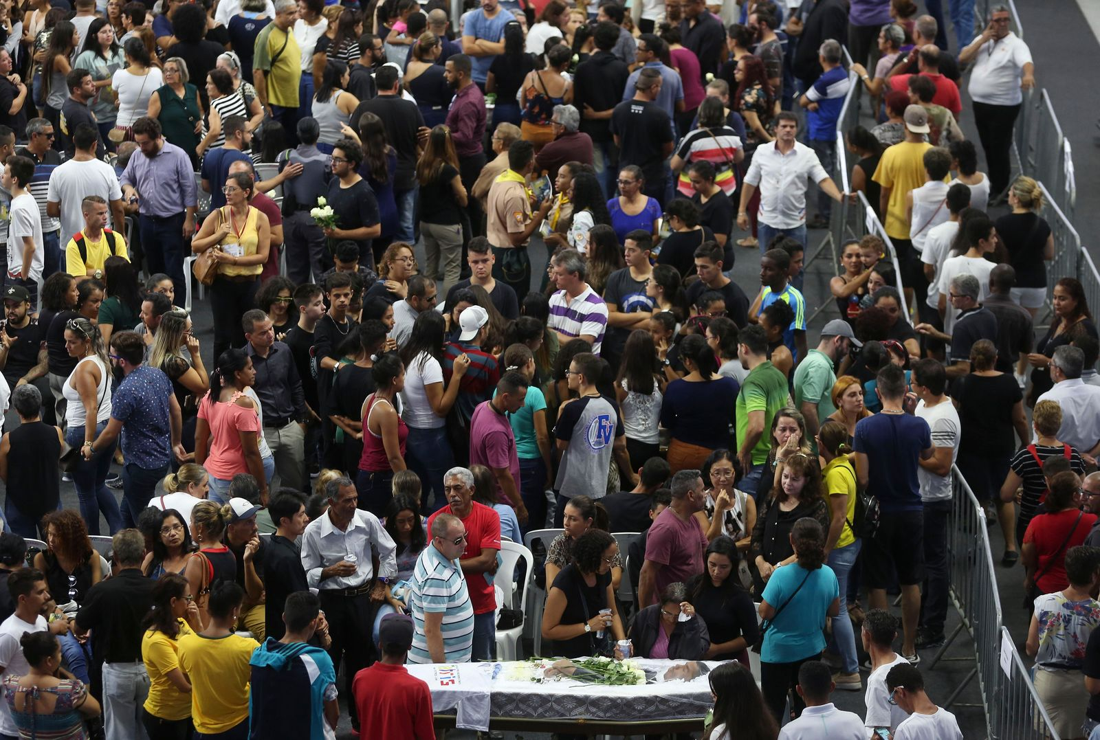 Relatives and friends pay their last respects as they walk past the coffin containing the remains of 17-year-old Claiton Antonio Ribeiro, a victim of the mass shooting at the Raul Brasil State School, in Suzano, Brazil, Thursday, March 14, 2019. (AP Photo/Andre Penner)