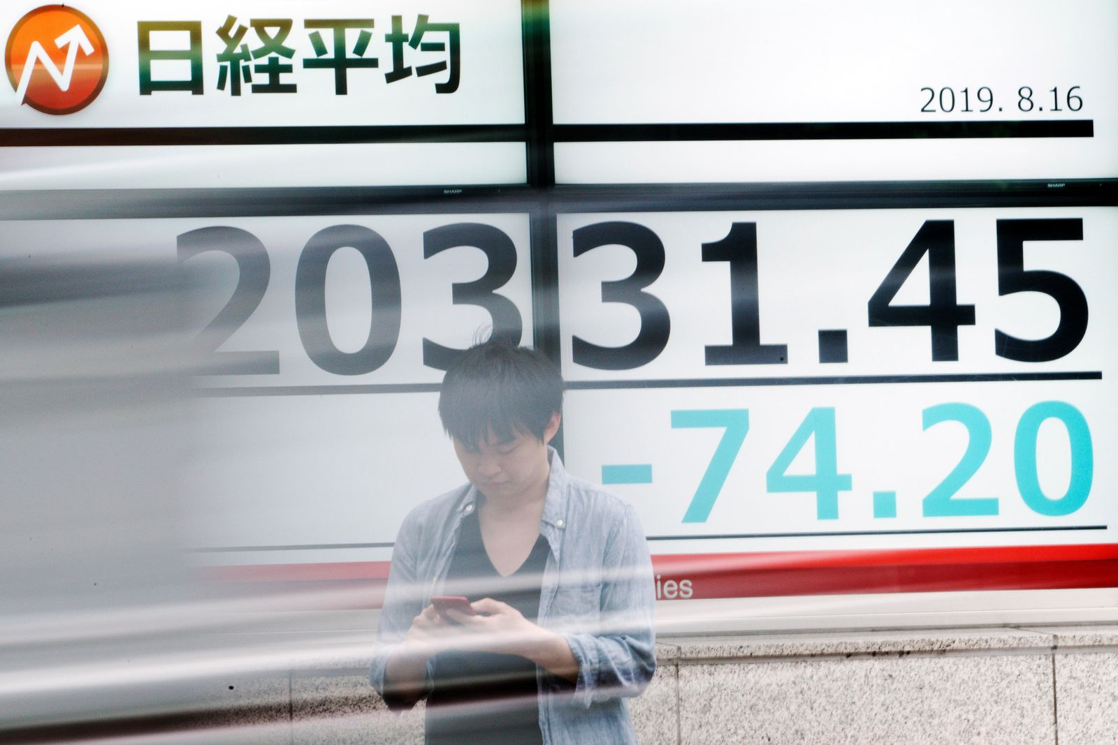 A man stands as a car goes by an electronic stock board showing Japan's Nikkei 225 index at a securities firm in Tokyo Friday, Aug. 16, 2019. Asian shares were mixed Friday as turbulence continued on global markets amid ongoing worries about U.S.-China trade conflict. (AP Photo/Eugene Hoshiko)