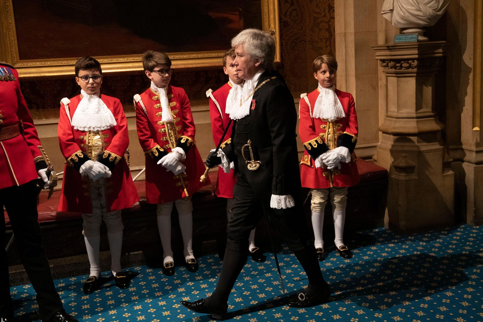 Black Rod, Sarah Clarke the first woman to serve in the role of Black Rod, walks past page boys in the Norman Porch at the Palace of Westminster and the Houses of Parliament for the State Opening of Parliament ceremony in London, Monday, Oct. 14, 2019. (AP Photo/Matt Dunham, Pool)