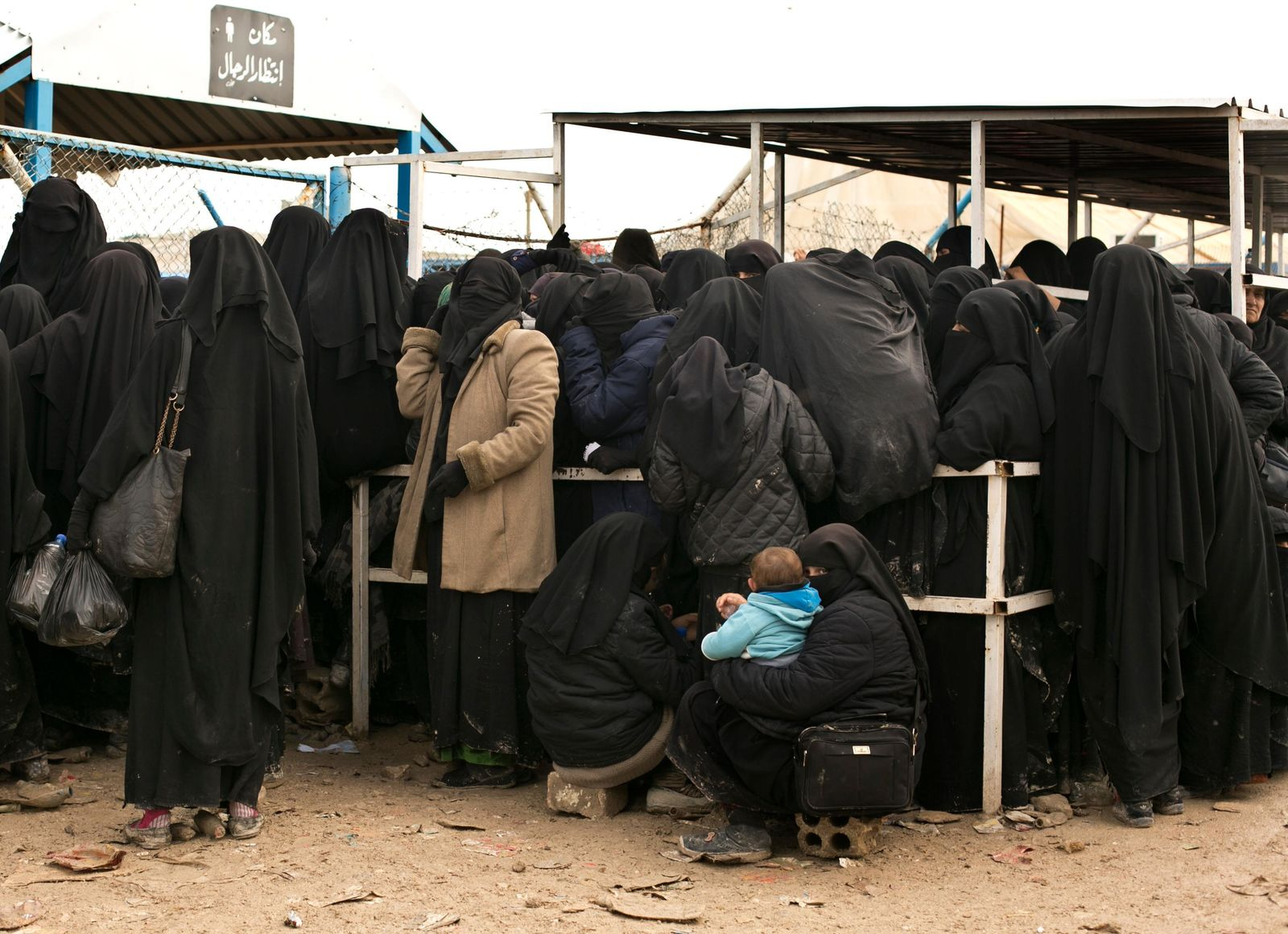 FILE - In this March 31, 2019 file photo, women residents from former Islamic State-held areas in Syria line up for aid supplies at Al-Hol camp in Hassakeh province, Syria. Syrian Kurdish forces said Monday, Oct. 28, 2019 they are beefing up security in prisons and detention facilities where tens of thousands of Islamic State militants and supporters are held, including foreigners, following the killing of the extremist group's leader. (AP Photo/Maya Alleruzzo, File)