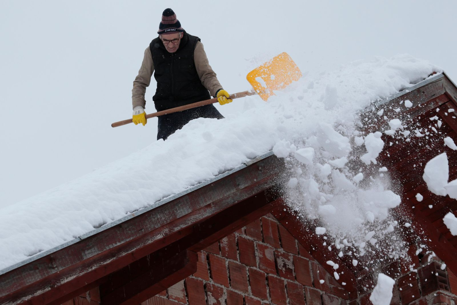A man shovels snow from the roof of his house in a remote village near Kladanj, 80 kms north of Sarajevo, Bosnia, Friday, Jan. 11. (AP Photo/Amel Emric)