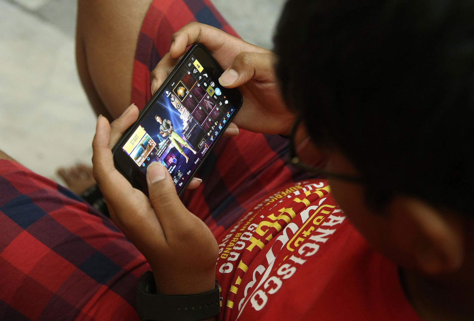 An Indian boy plays an online game PUBG on his mobile phone in Hyderabad, India, Friday, April 5, 2019.{ } (AP Photo/ Mahesh Kumar A.)