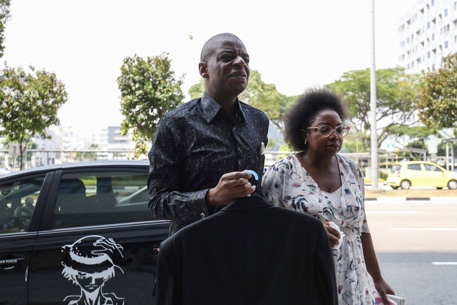 Adam Molai, left, and a relative arrive at the Singapore Casket funeral parlor building where the body of the late former president of Zimbabwe is being held on Saturday, Sept. 7, 2019, in Singapore.{ } (AP Photo/Danial Hakim)