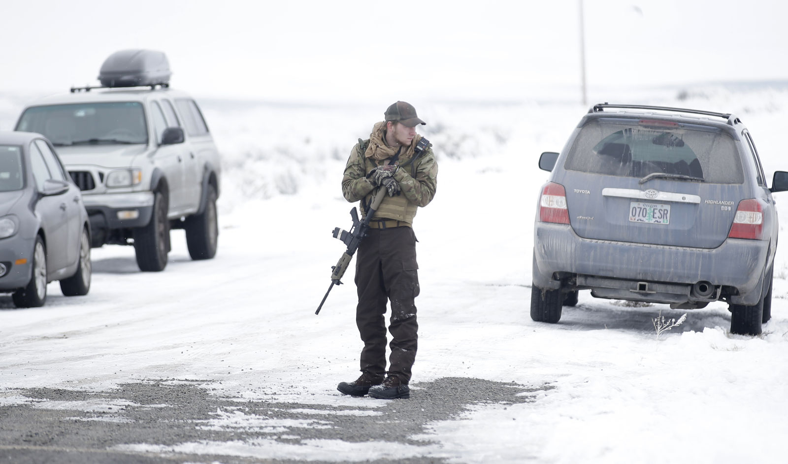 "A man stands guard after members of the ""3% of Idaho"" group along with several other organizations arrived at the Malheur National Wildlife Refuge near Burns, Ore., on Saturday, Jan. 9, 2016. A small, armed group has been occupying the remote national wildlife refuge in Oregon for a week to protest federal land use policies. (AP Photo/Rick Bowmer)"