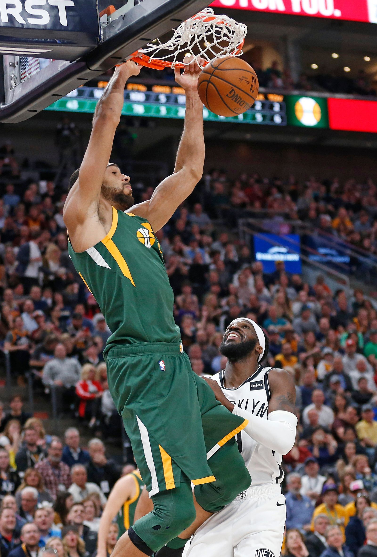 Utah Jazz center Rudy Gobert, left, dunks as Brooklyn Nets forward DeMarre Carroll, rear, looks during the first half during an NBA basketball game Saturday, March 16, 2019, in Salt Lake City. (AP Photo/Rick Bowmer)