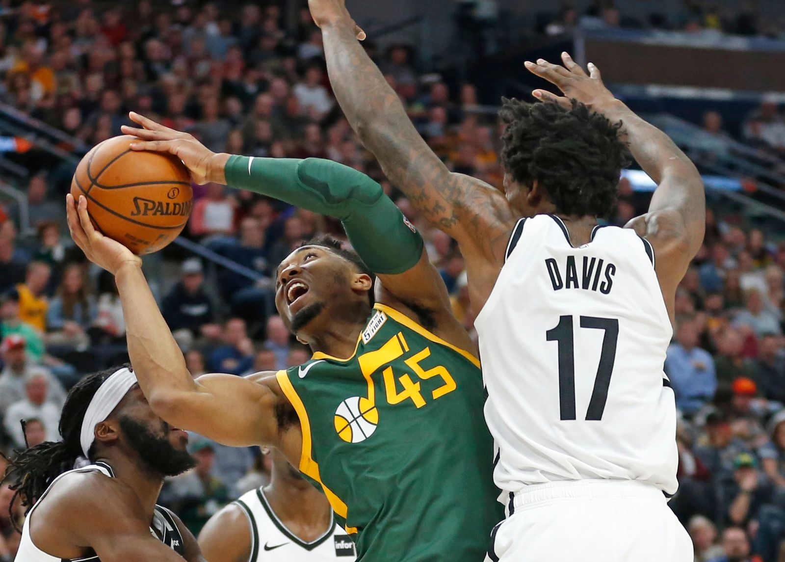 Utah Jazz guard Donovan Mitchell (45) goes to the basket as Brooklyn Nets forward Ed Davis (17) defends during the first half of an NBA basketball game Saturday, March 16, 2019, in Salt Lake City. (AP Photo/Rick Bowmer)