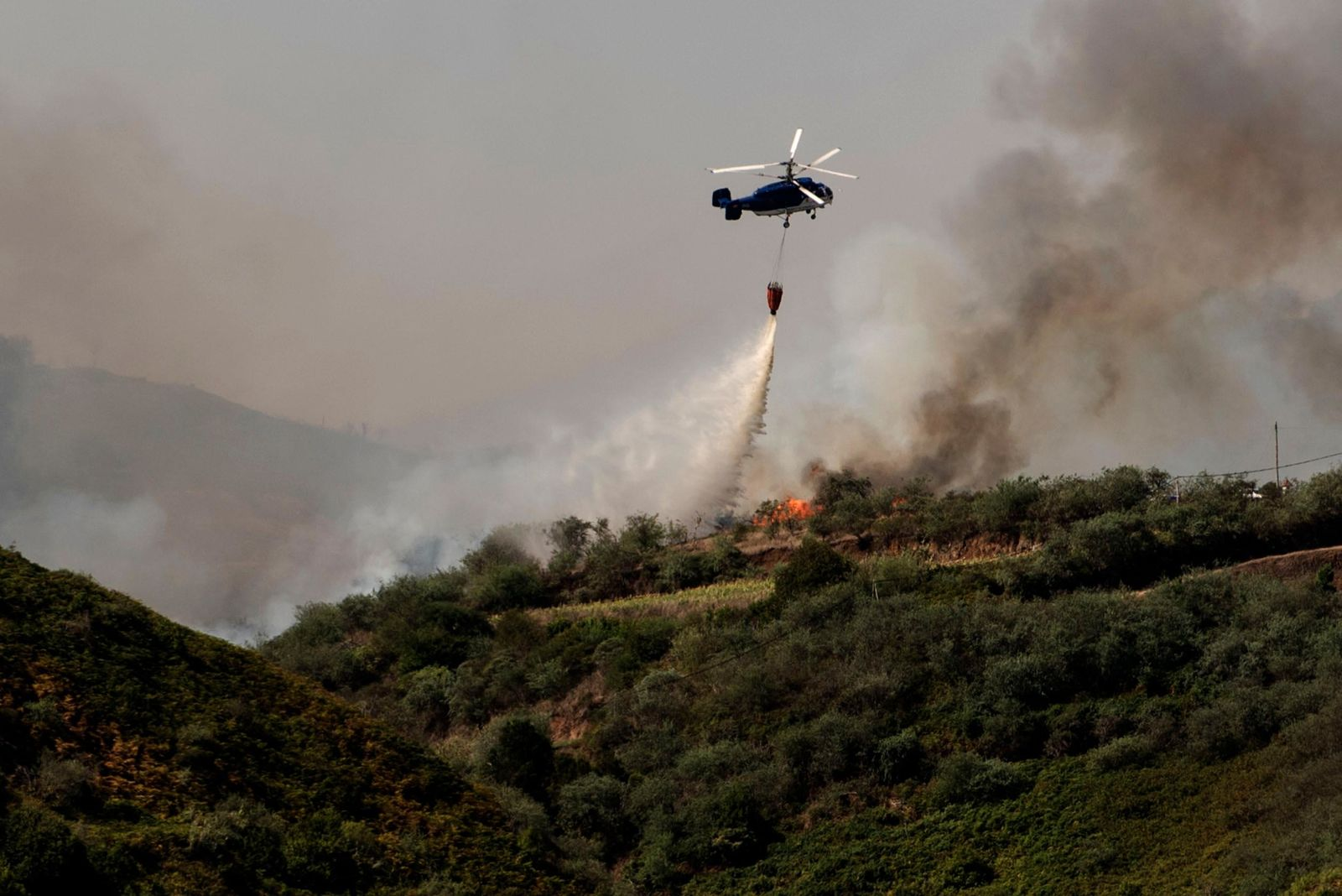 A helicopter operates over a wildfire in Canary Islands, Spain, Monday, Aug. 19, 2019. . (AP Photo/Arturo Jimenez)