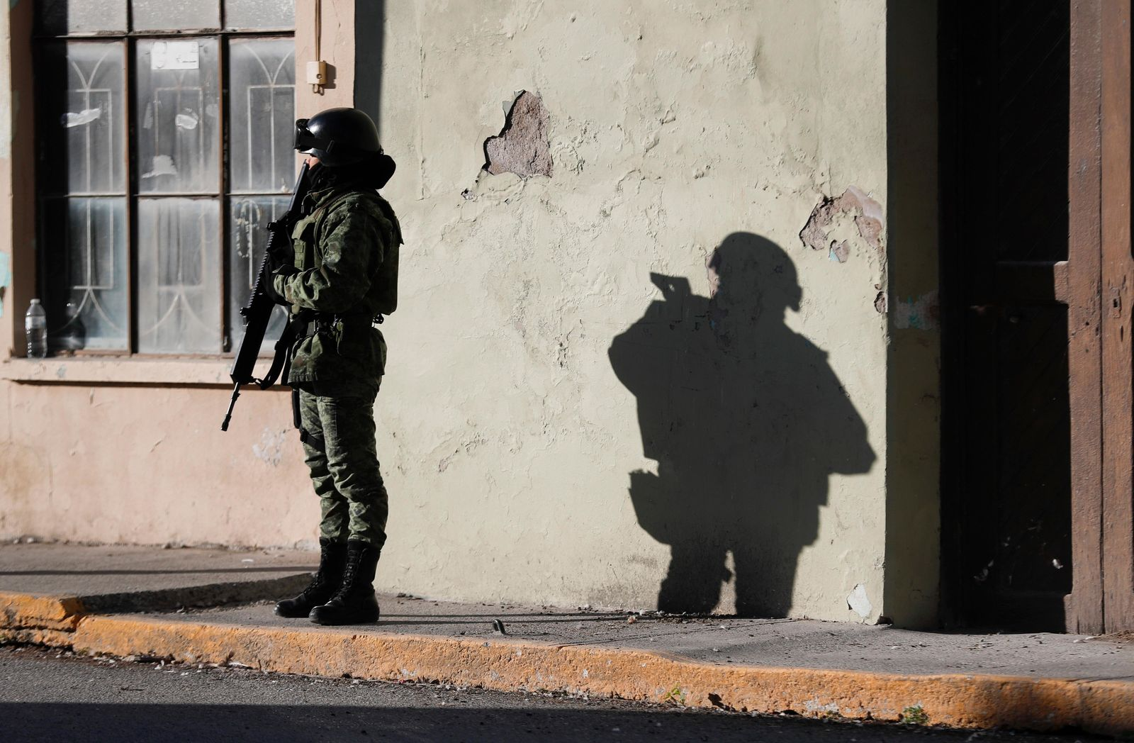 "A member of the Mexican security forces stands guard near City Hall in Villa Union, Mexico, Tuesday, Dec. 3, 2019. Some long for the days when Mexican marines successfully patrolled the area until President Andres Manuel Lopez Obrador reassigned them to other duties. They were known for not getting corrupted by the cartels and not yielding in battle with them. ""The marines are the only ones I trust,"" said one local mechanic. ""The rest are going to take a bribe.""  (AP Photo/Eduardo Verdugo)"