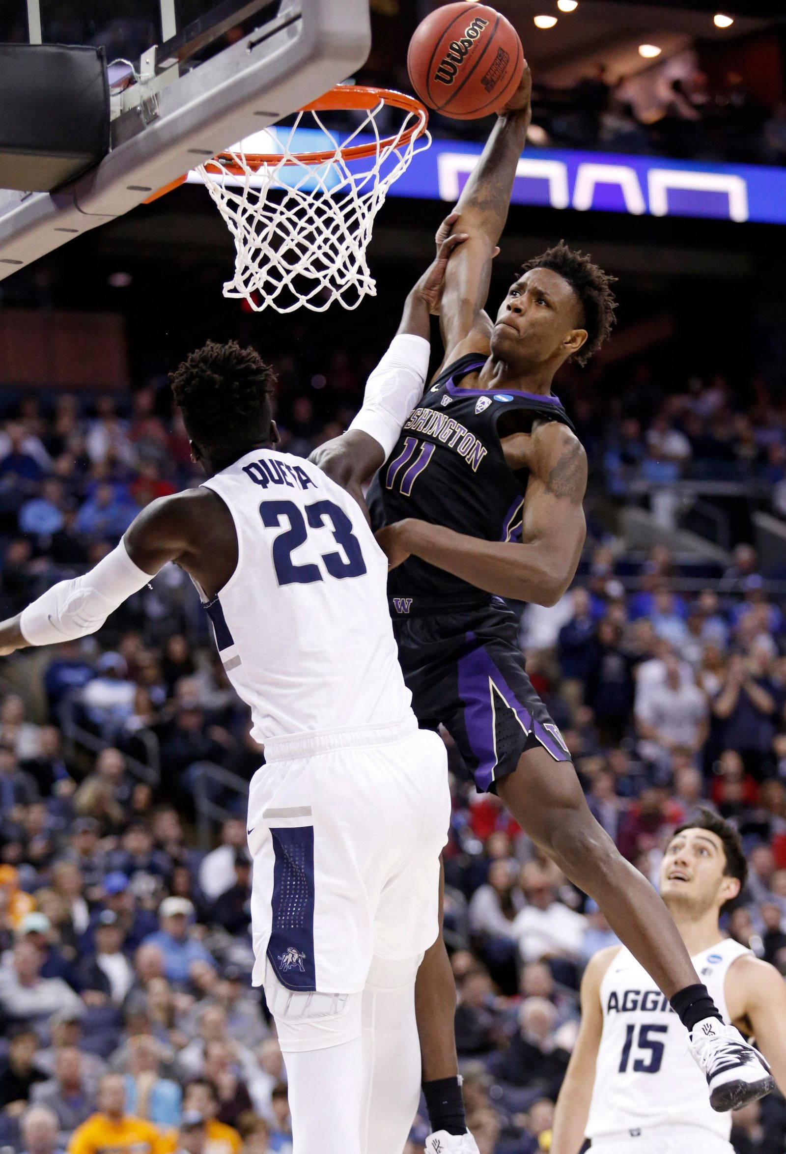 Washington's Nahziah Carter (11) dunks over Utah State's Neemias Queta (23) in the second half during a first round men's college basketball game in the NCAA Tournament in Columbus, Ohio, Friday, March 22, 2019. (AP Photo/Paul Vernon)