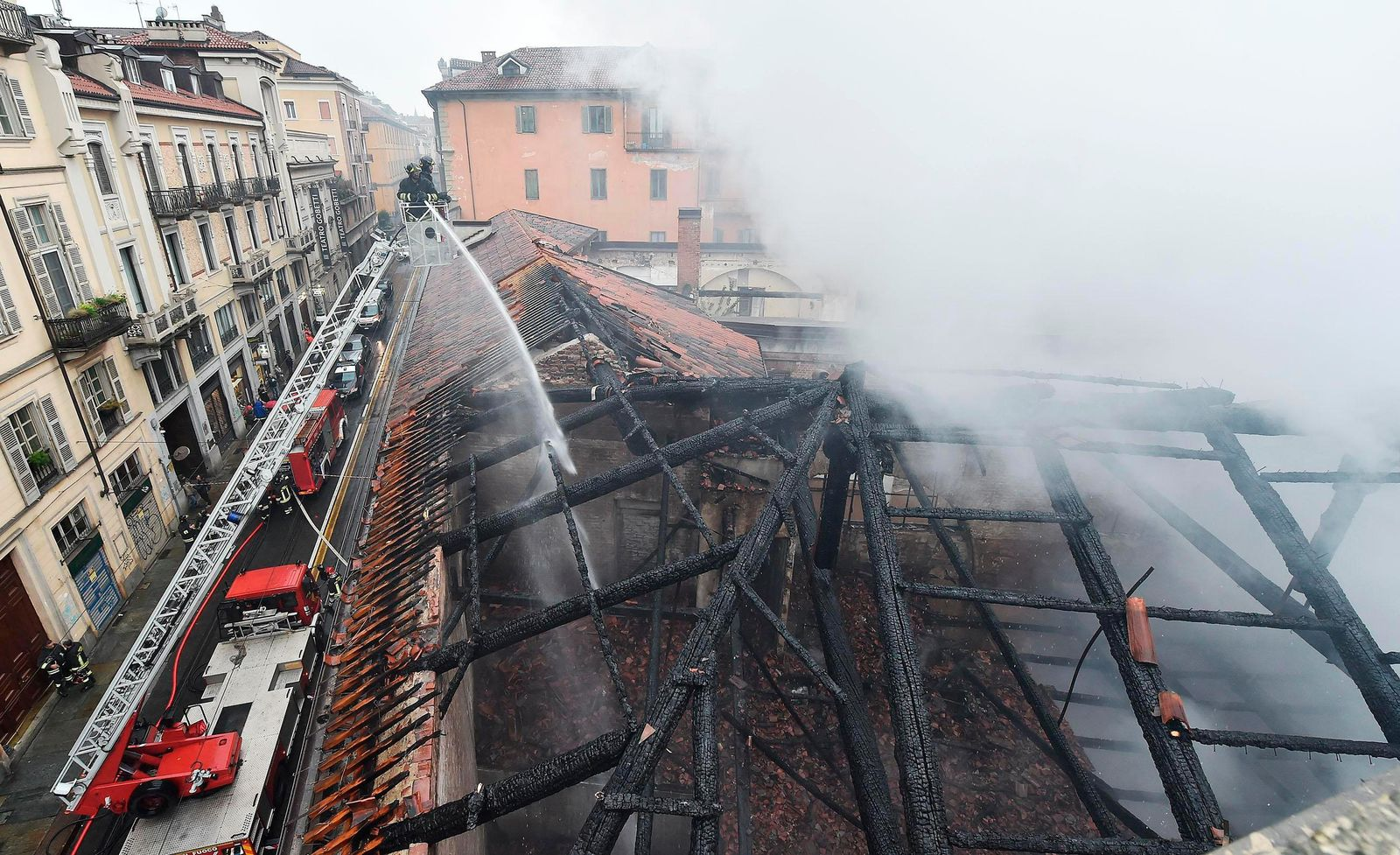 Firefighters put out a fire on the rooftop of the Cavallerizza Reale, in Turin, northern Italy, Monday, Oct. 21, 2019. (Alessandro Di Marco/ANSA via AP)