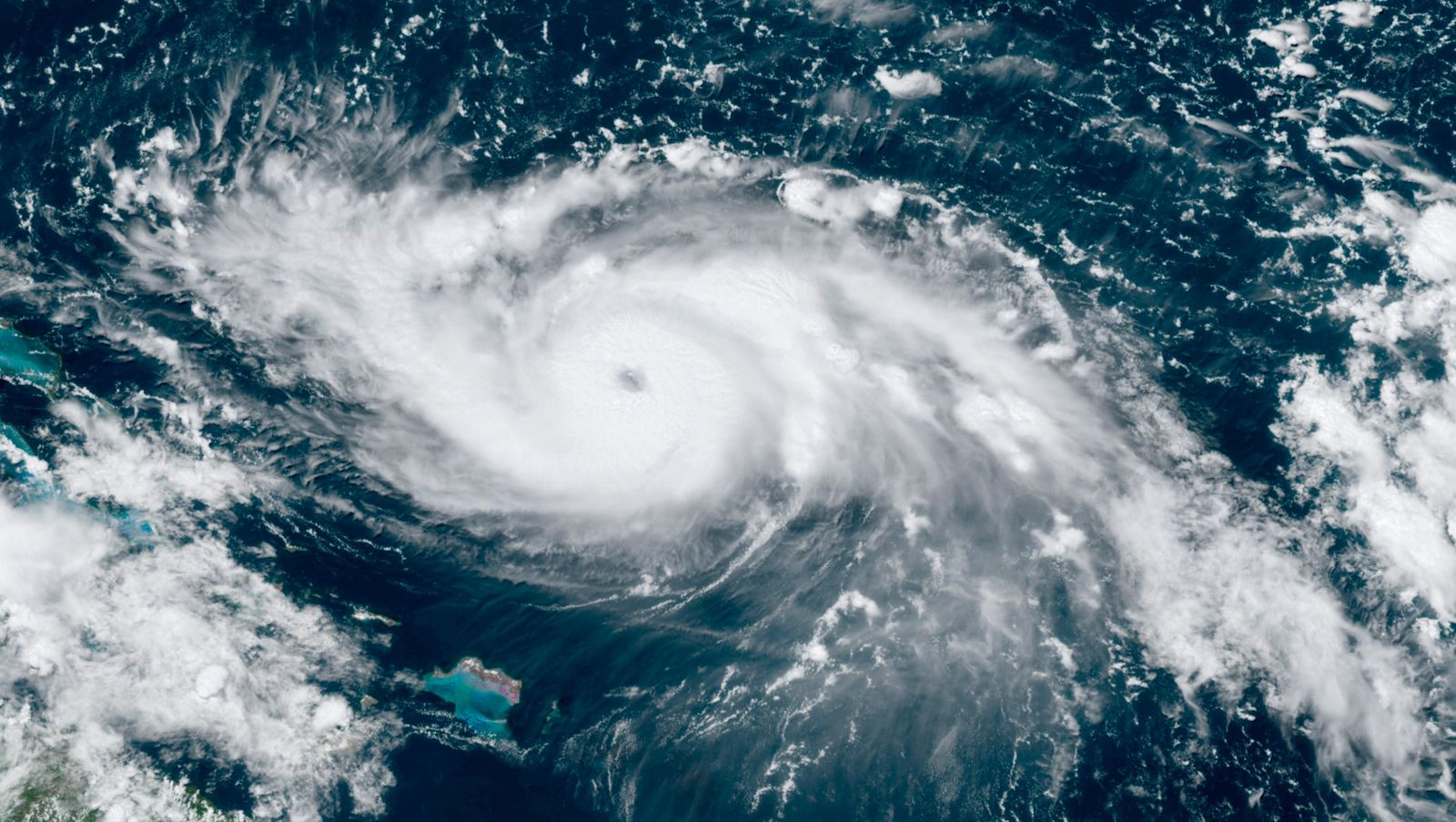 This GOES-16 satellite image taken Friday, Aug. 30, 2019, at 17:30 UTC and provided by National Oceanic and Atmospheric Administration (NOAA), shows Hurricane Dorian, right, moving over open waters in the Atlantic Ocean. Forecasters are now saying Dorian could be a Category 4 with winds of nearly 140 mph (225 kph) when it is forecasted to hit Florida late Monday or early Tuesday. It's also imperiling the Bahamas, where the storm is expected to hit by Sunday. (NOAA via AP)