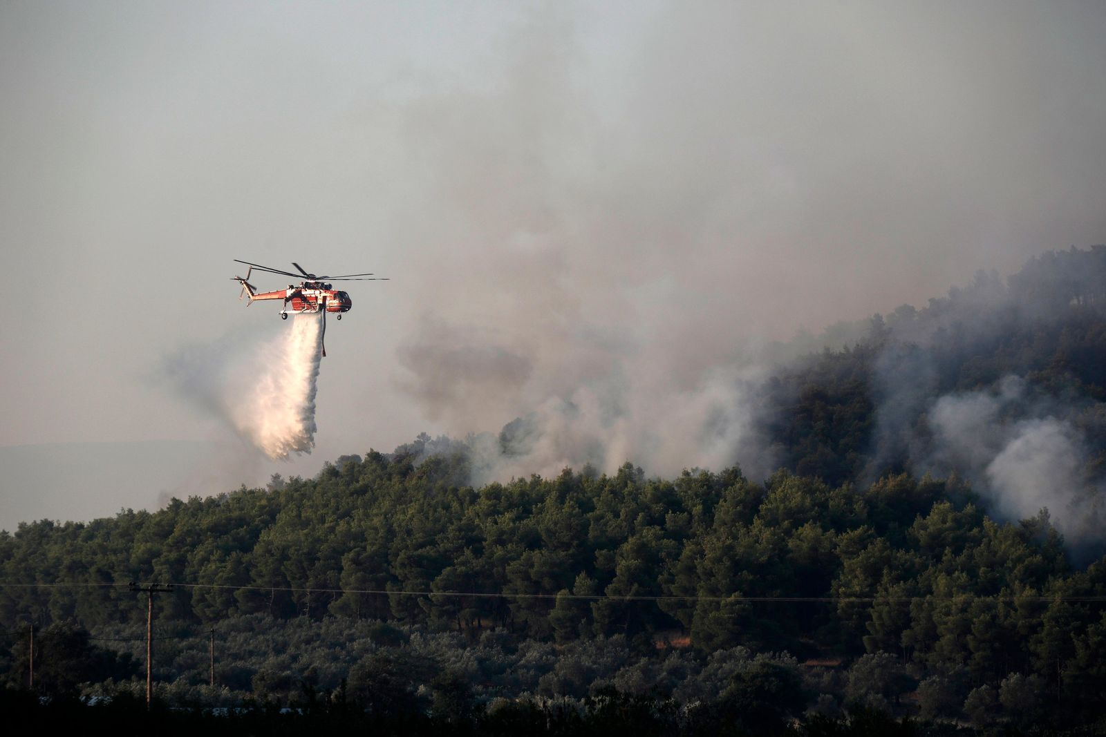 File- An helicopter operates over a wildfire in Makrymalli village on the Greek island of Evia, Wednesday, Aug. 14, 2019. (AP Photo/Yorgos Karahalis)