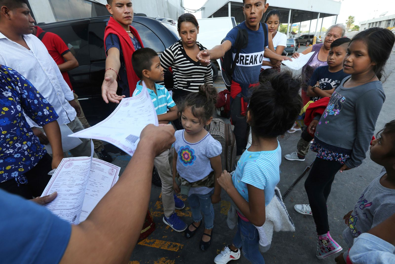 Pastor Aaron Mendes hands out documents to Migrants before they enter the immigration office on the Mexican side of the border, before they are escorted across to apply for asylum on the United States side, in Nuevo Laredo, Mexico.{ } (AP Photo/Marco Ugarte)