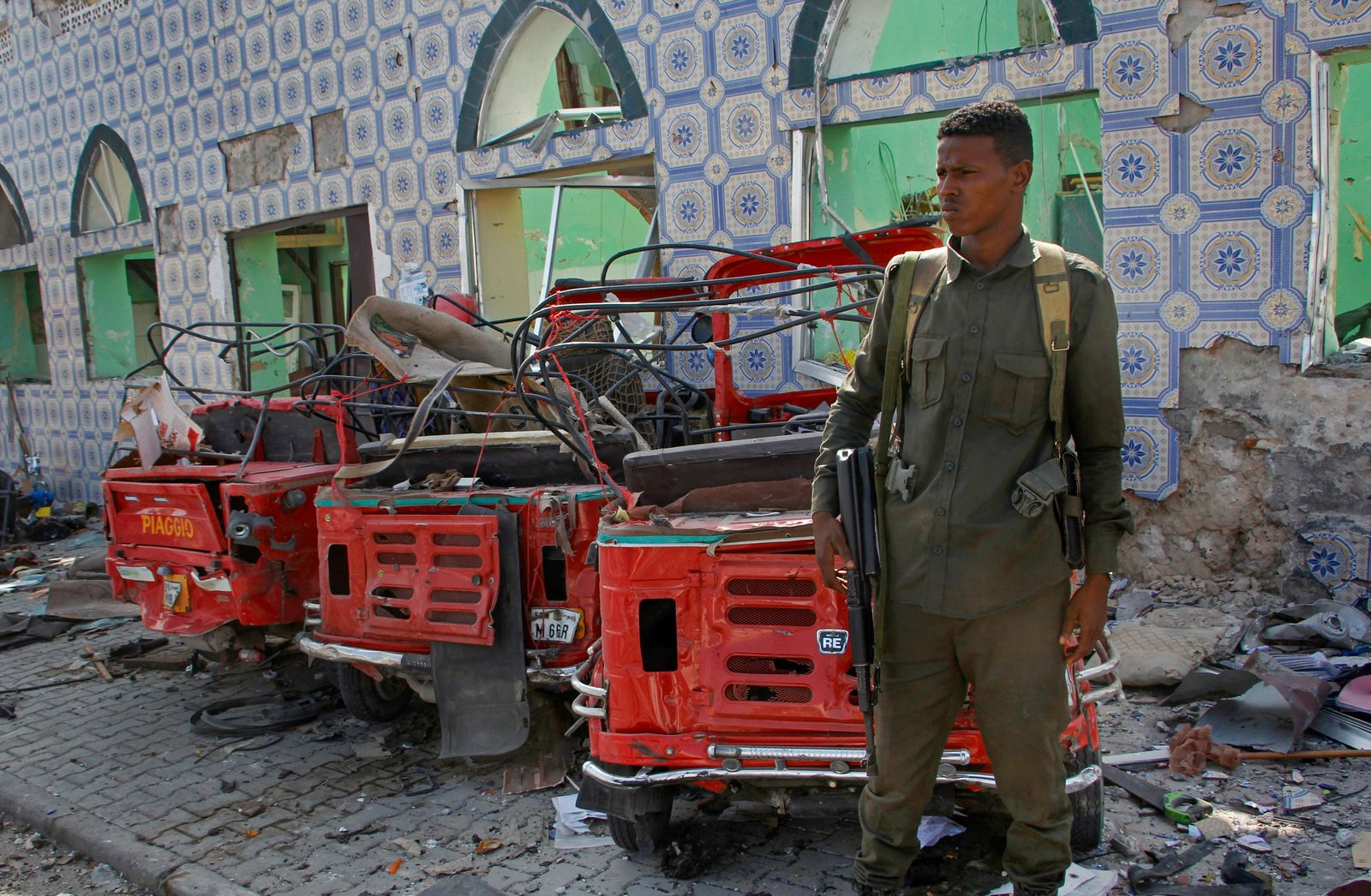 Security forces stand near the wreckage of three-wheeled vehicles destroyed in a bomb attack in the capital Mogadishu, Somalia Saturday, June 15, 2019. (AP Photo/Farah Abdi Warsameh)